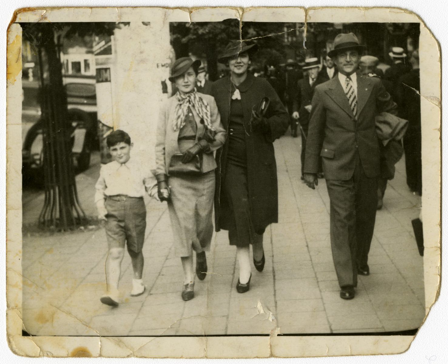 Mark Steil walks down a street in Antwerp with his parents, Adolf and Eliza Steil, and another woman.