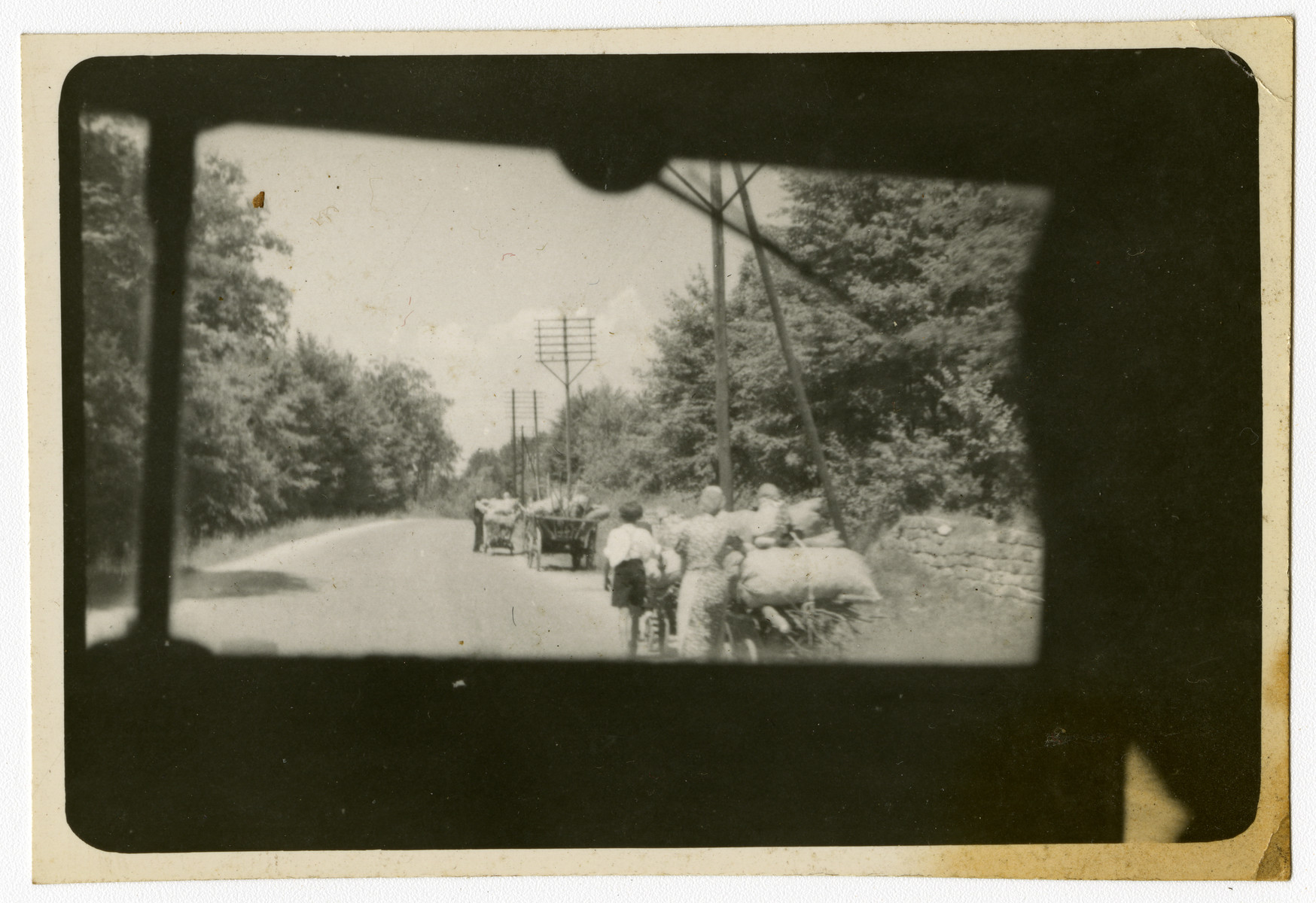 "Photograph taken through the window of a vehicle showing refugees hauling personal belongings on their way home.  Original caption reads, ""Refugees, 1945."""