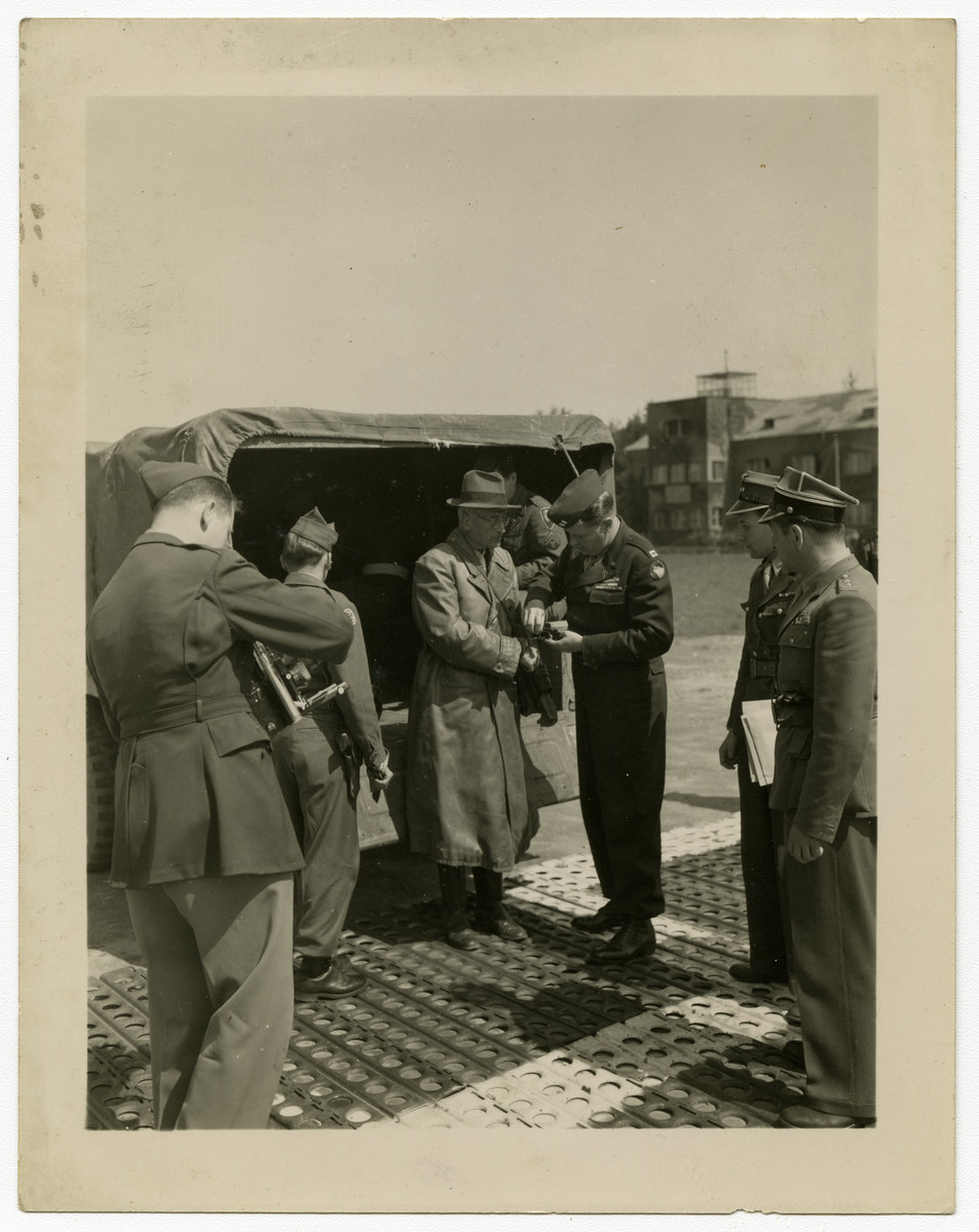 "Kurt von Burgsdorff is brought in handcuffs to the airport to be flown to Poland for trial as a war criminal.  Original caption reads, ""Dr. Kurt Von Burgsdorff, former Governor of Kracow, Poland, under the Nazi Regime, is having his handcuffs changed by Captain Binder as two Polish officers look on. Burgsdorff, with two other Ex-Nazi officials, were being held at Nurnberg, Germany as witnesses at the International Military Tribunal trials. Burgsdorff, along with the other two men in Nurnberg, were met by seven other defendants flown from Frankfurt by the AAF Airport to Furth, Nurnberg, making a total of ten men being turned over by the Americans to the Polish Government to be tried as war criminals.""   The photo is dated 25 May and is credited to photographer PFC Eddie Murphy of the U.S. Army Signal Corps."