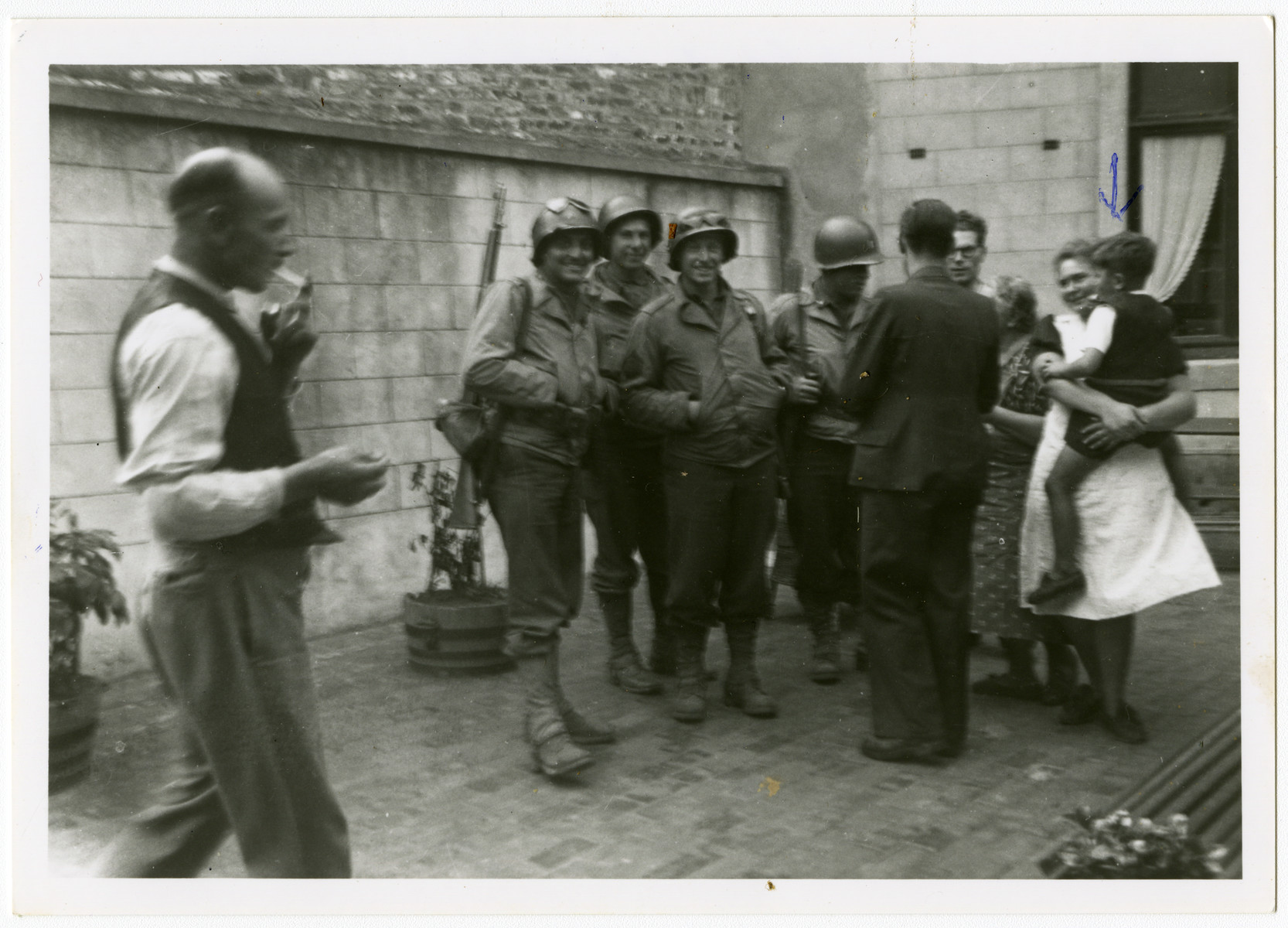 American soldiers liberate the town of Perwez.  Pictured on the right is Mrs. Hemptine Stas, the wife fo the butcher, who was hiding the Jewish child Albert Szabo who she is holding.  She lived next door to the Henrards, the rescuers of Simon Steil.