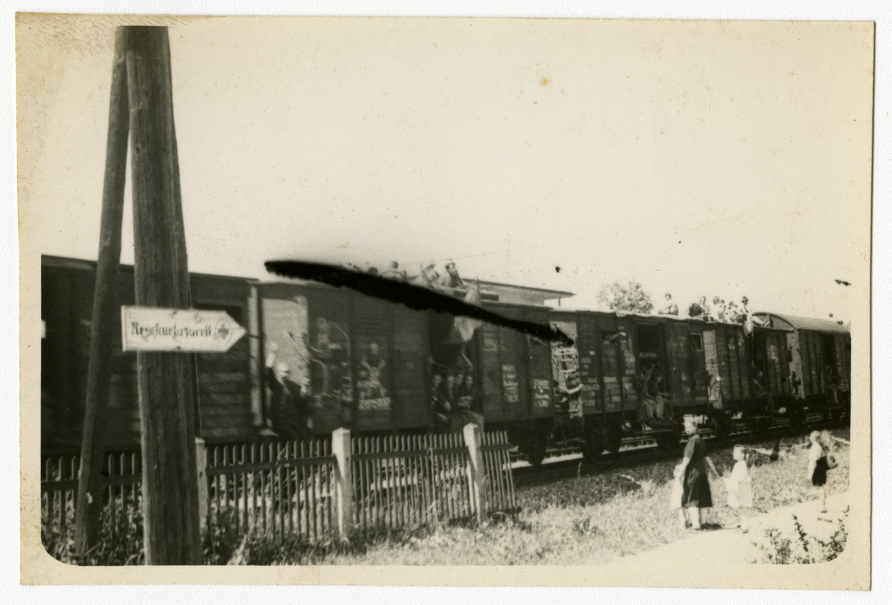 "Russian refugees wave from a train on their return to the Soviet Union.  Original caption reads, ""Russian Refugees going home."""