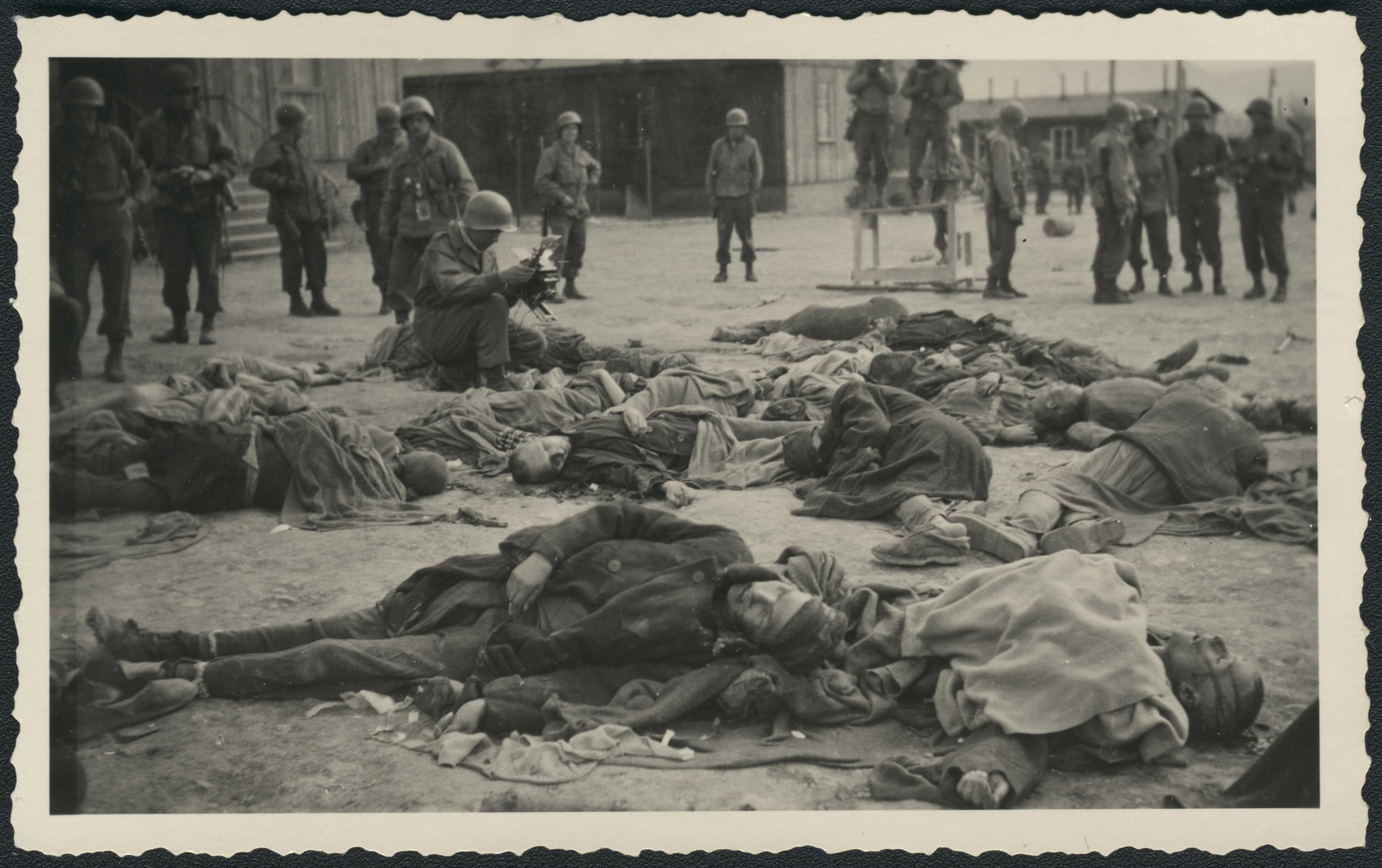 American soldiers take photographs of corpses lying on the ground of the newly liberated Ohrdruf concentration camp.
