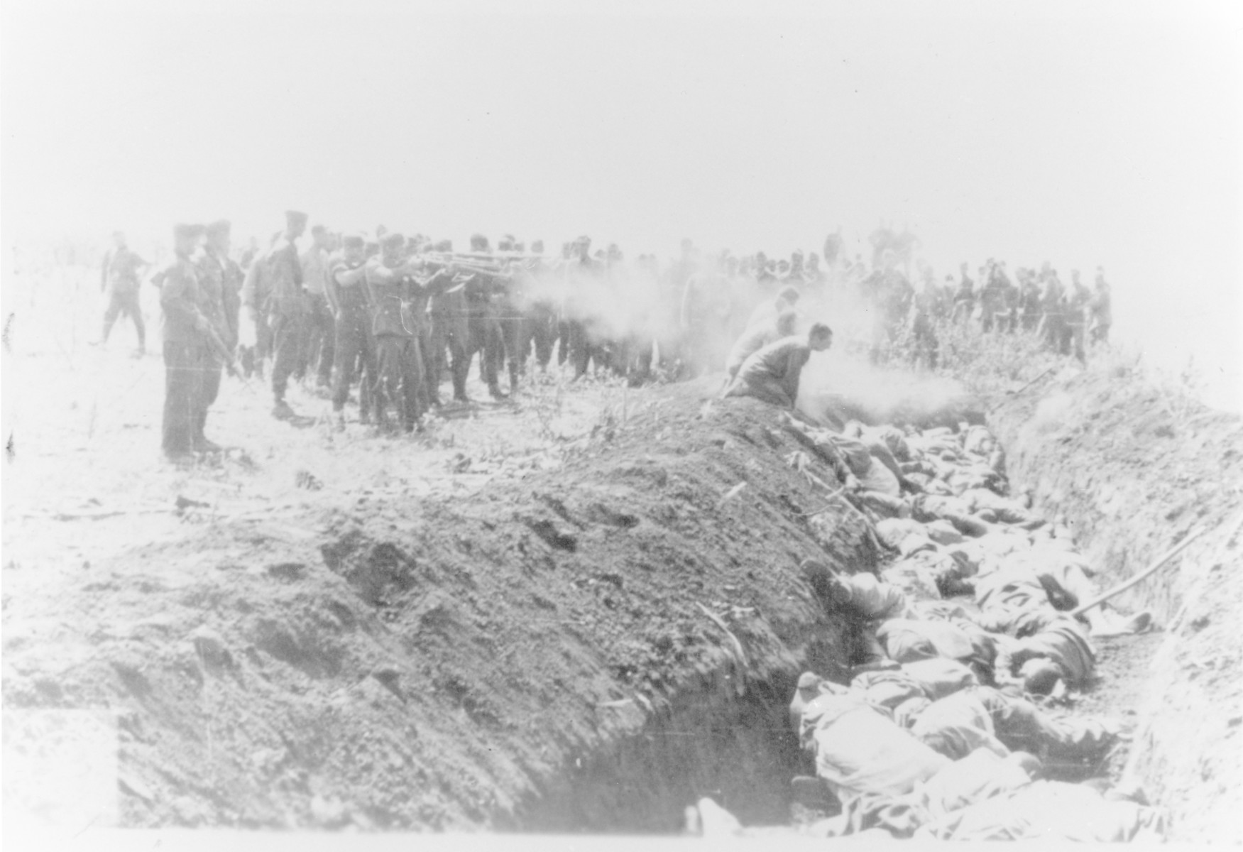 Men with an unidentified unit execute a group of Soviet civilians kneeling by the side of a mass grave.