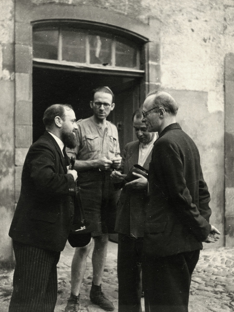 Leo Cohn (father of the donor) and three men have a conversation outside of a building, probably on a farm.  Leo is wearing his Eclaireurs Israelites uniform.   Jacob Gordon is on the right.