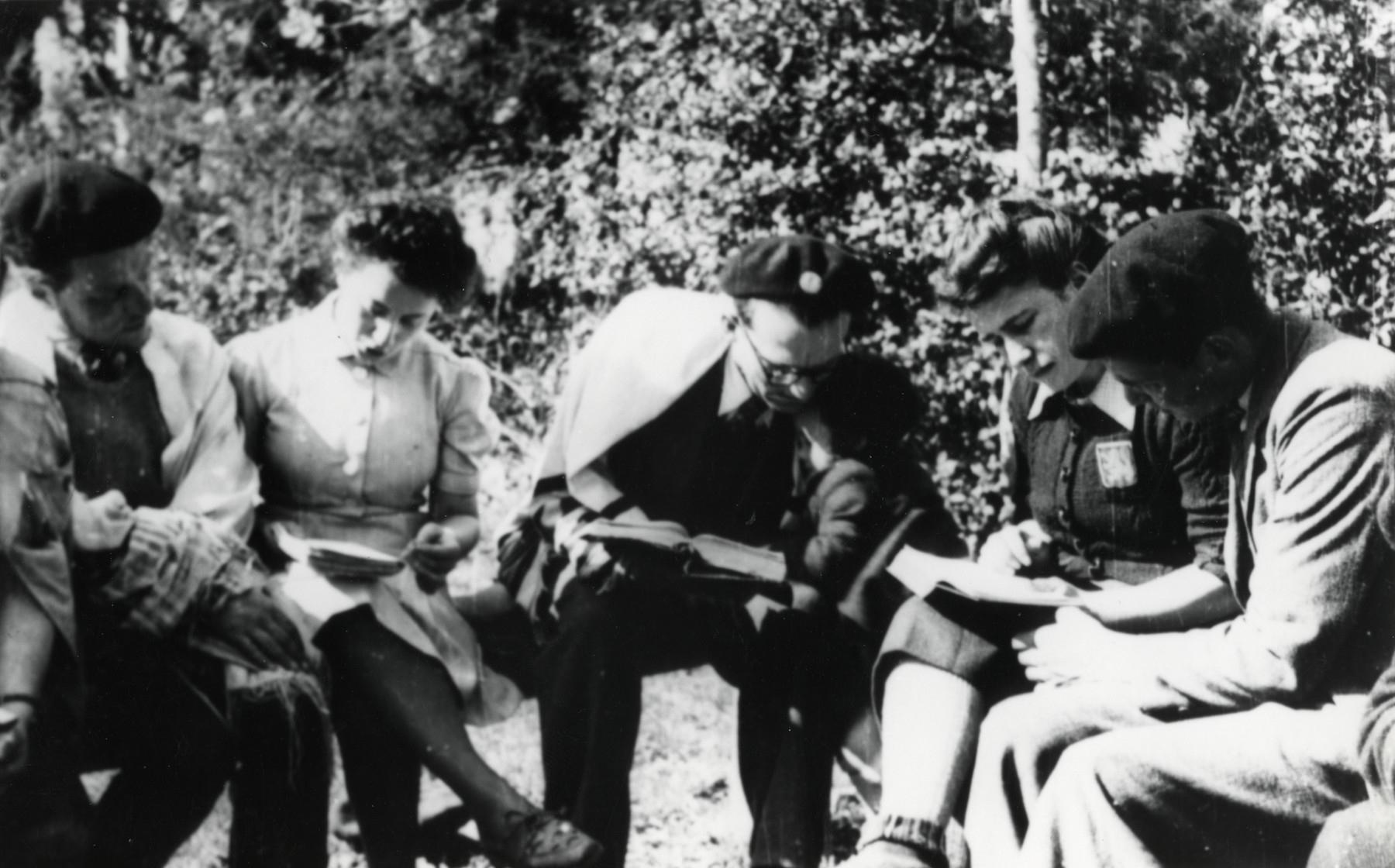 A group of five persons studies outdoors.   Pictured in the center is Noemi Cassuto, aged 3 or 4. Her father, Leo Cohn, in a prayer shawl, bends down towards her.