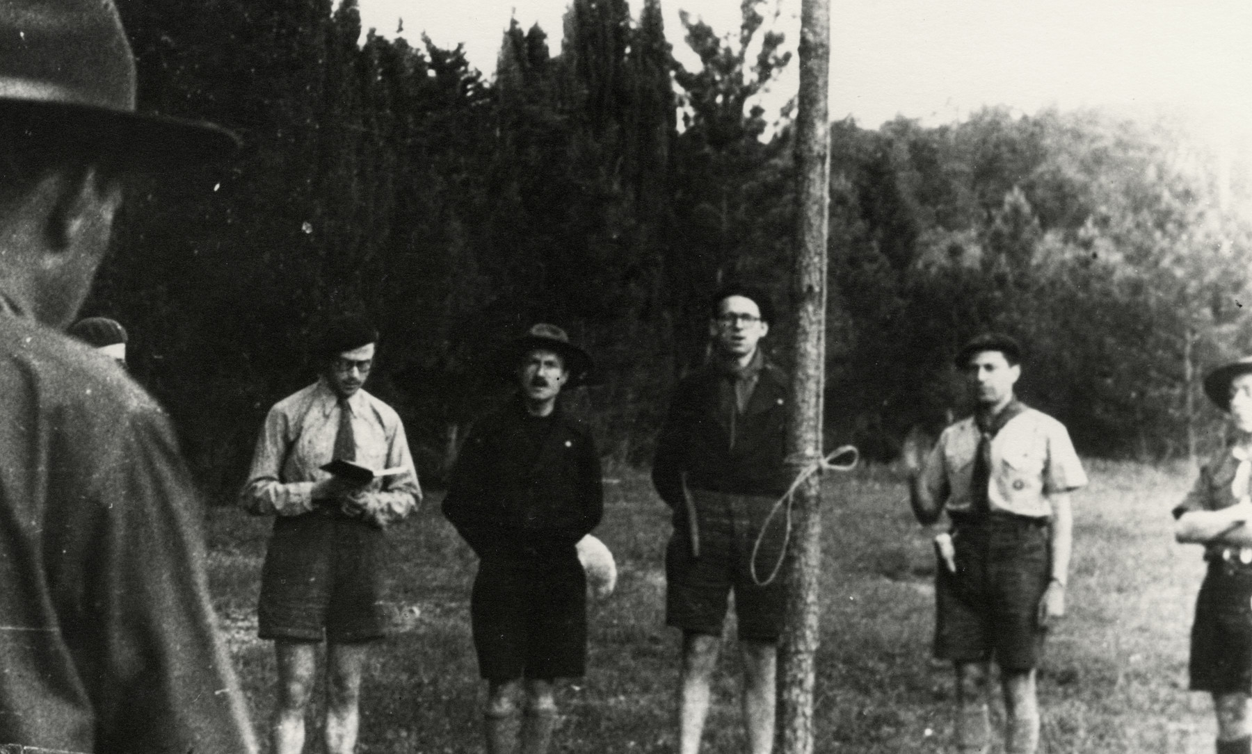Seven members of the Eclaireurs Israelites gather around a pole, maybe singing.   Pictured third from the right is Leo Cohn.