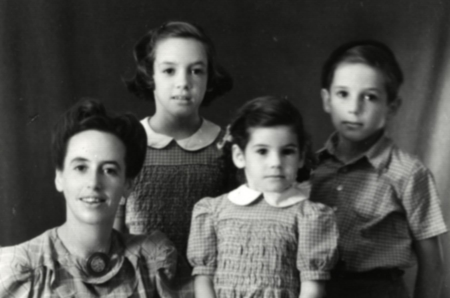 Studio portrait of Rachel Cohn and her three children, Noemi, Ariel and Aviva, upon their arrival in Palestine.