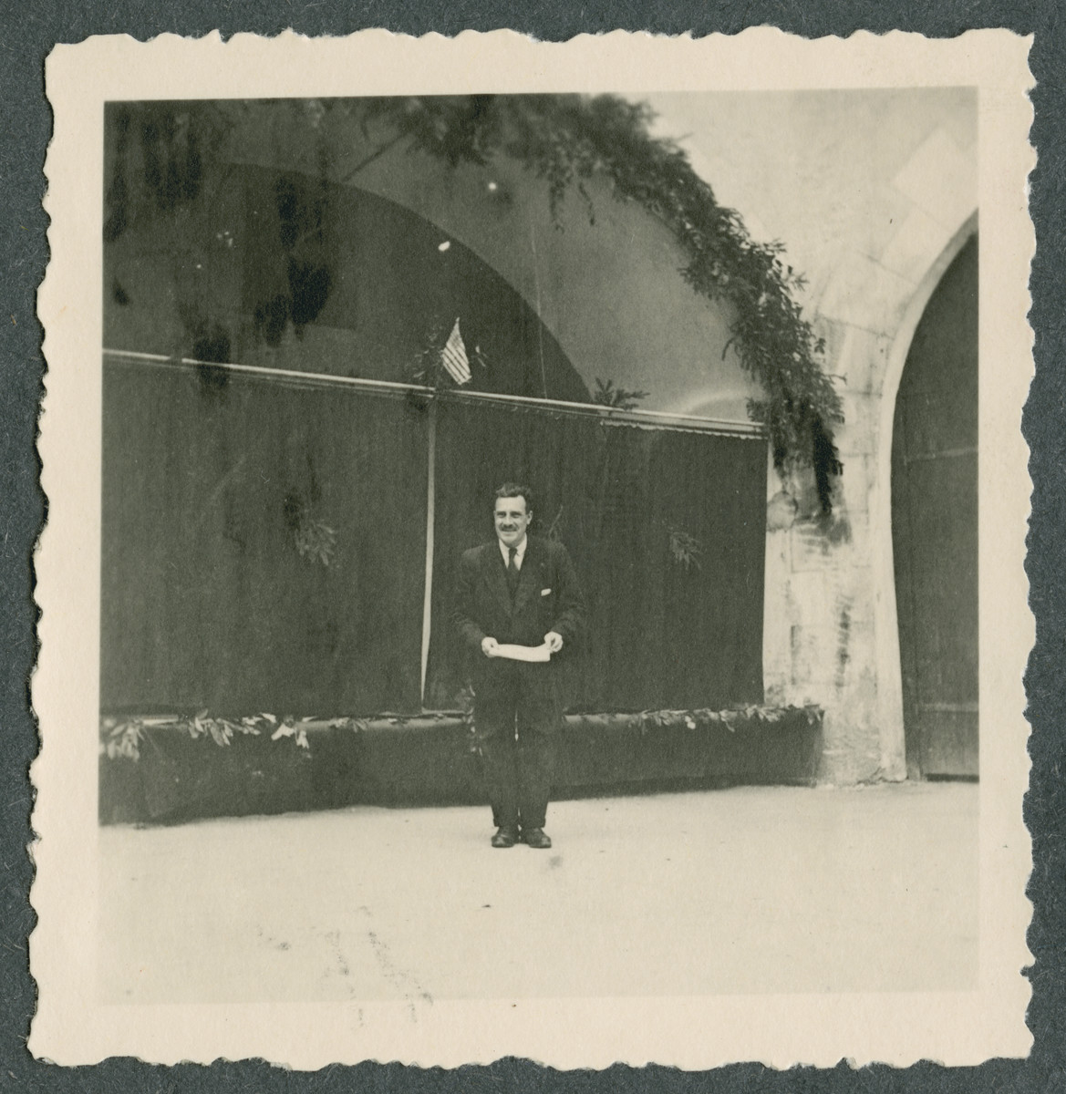 An unidentified prisoner stands underneath an American flag near the entrance to Tittmoning castle in preparation for one of the shows put on by prisoners.  Improvised stage curtains are behind him