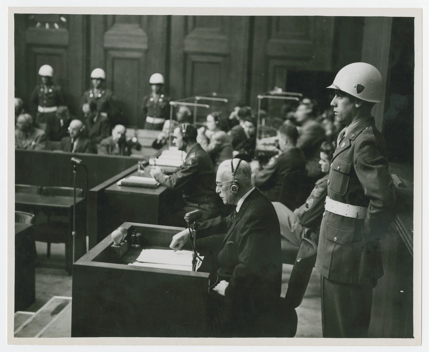 Konstantin von Neurath reads from a document during his trial for war crimes at Nuremberg.