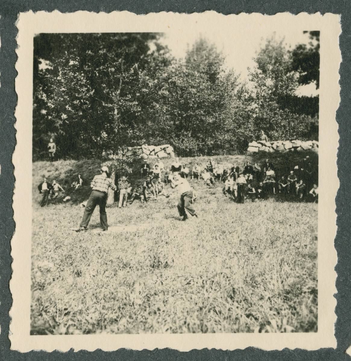 American prisoners play softball on the grounds of the Tittmoning camp while two armed guards watch from behind the hedge.  This was the first time that some of the prisoners from European countries had seen softball.