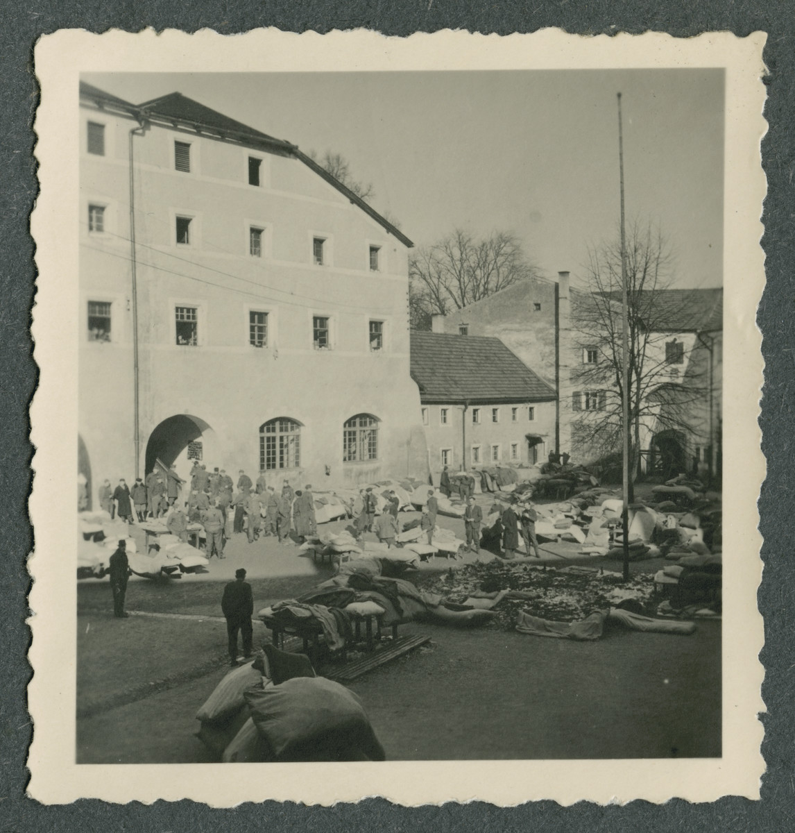 Prisoners either sort or open up bedding and bundles in the courtyard of Tittmoning castle.