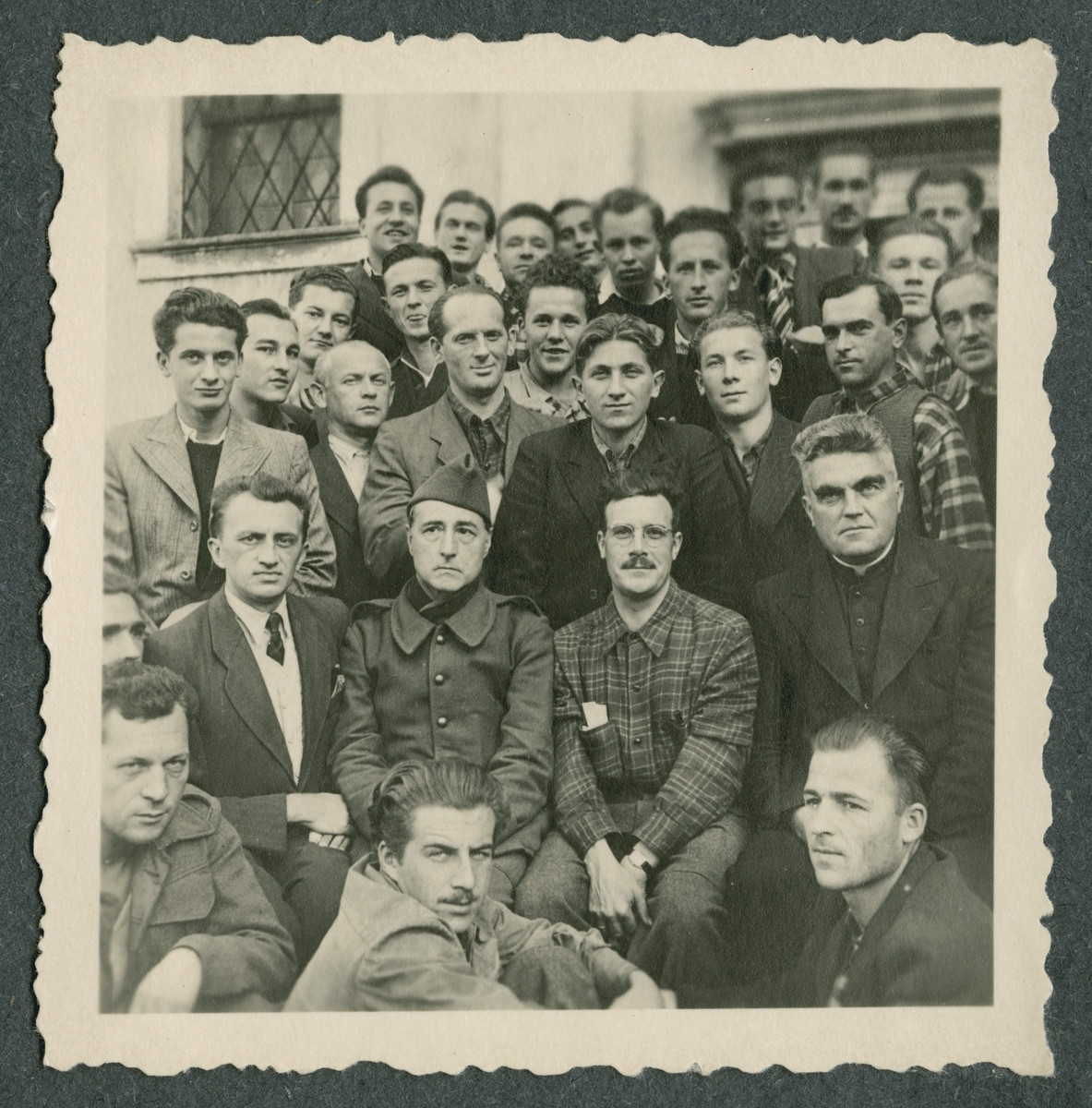 Group portrait of prisoners in Ilag VII, a camp for foreign nationals.  The man in the middle wearing the cap was a prisoner interpreter who could speak to the German authorities.  Father Sledz is in the priest's habit in the second row on the right