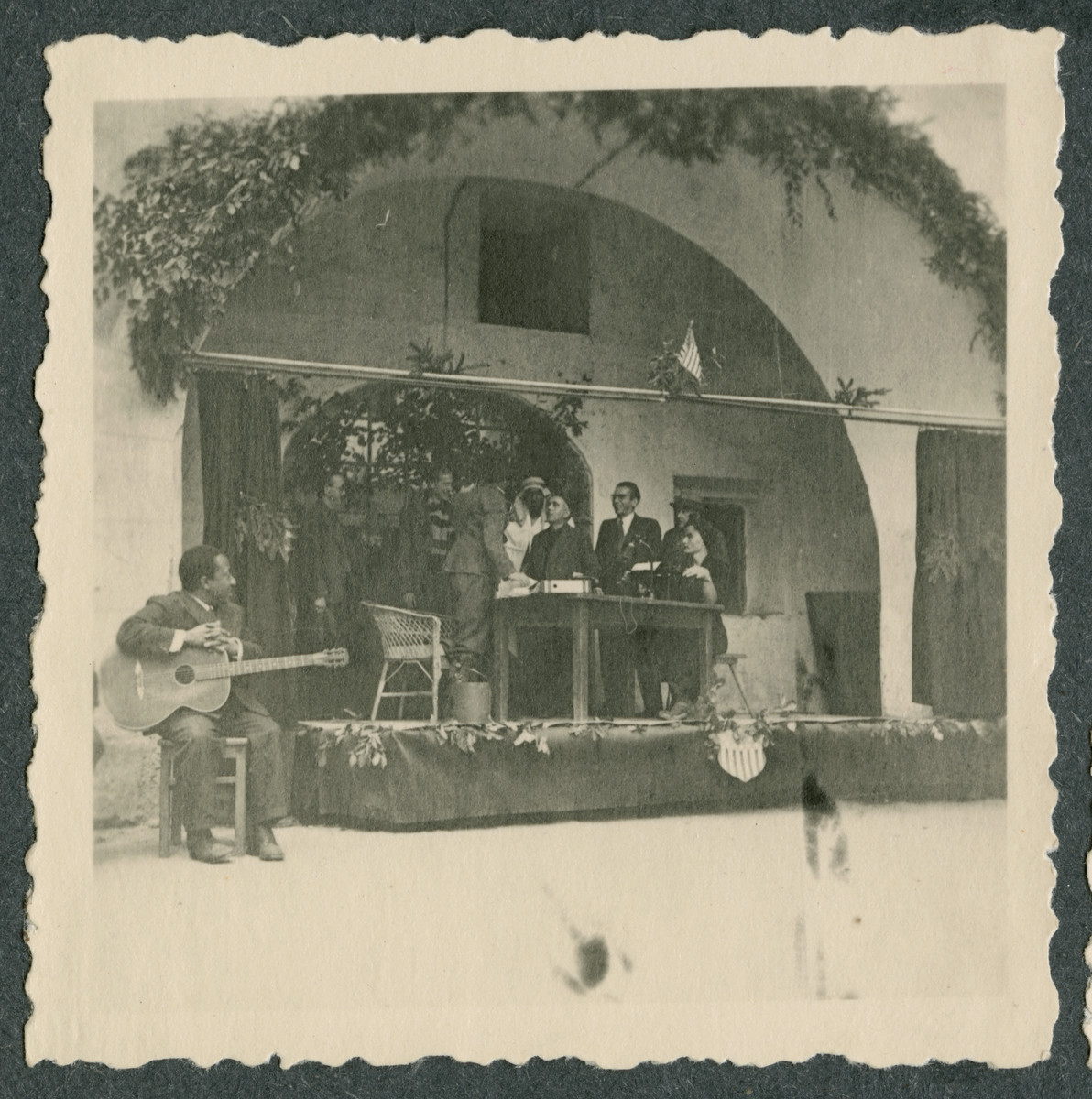 Internees gather by the entrance to Tittmoning castle underneath the American flag  for an official program.  Among those pictured is guitarist Johnny Mitchel, on the left.
