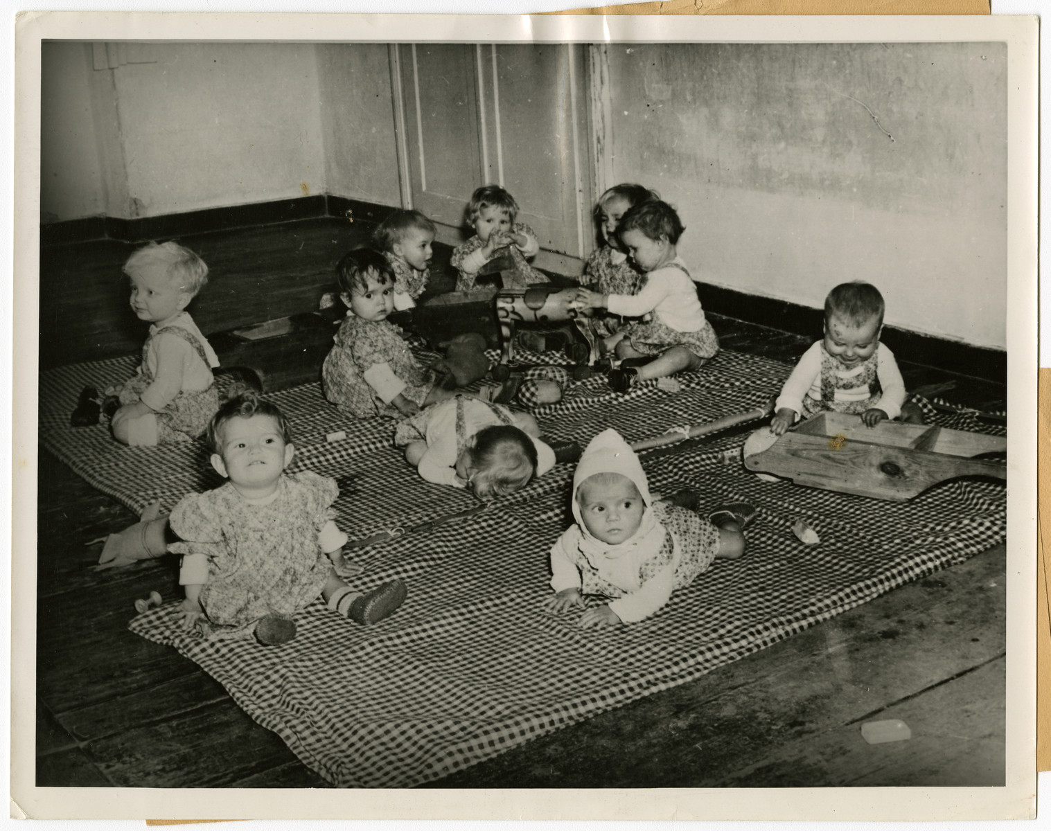 """Orphans, found by U.S. troops in Germany, play in the infant/toddler room of Kloster Indersdorf.  The original caption reads: """"Orphans of Indersdorf, Bavaria Orphans of 12 nations have found a new home in a former nunnery at Indersdorf, Bavaria, where UNRRA (United Nations Relief and Rehabilitation Administration) recently opened an international refuge for children found by the U.S. Army in Germany. Hundreds of helpless children whose parents were killed or lost during the war were sent from Nazi foreign labor and concentration camps to this institution. Two- thirds of the group are Polish and Jewish. Some are too young to remember their parents and others do not know their own names. Most of these from the concentration camps have no other identification than a number and the letters """"KL"""" (Konzentrations Lager) marked on their skins. When children arrive at the institution, they are deloused, bathed and given clean clothes. Medical attendants then innoculate them against typhoid fever, diptheria, and smallpox. The infants are cared for by nurses while older children begin elementary education in their own language under teachers of the Allied nations.   This photo shows: Orphan children, found by the U.S. troops advancing into Germany during the war, frolic happily in the playroom of the institution."""""""