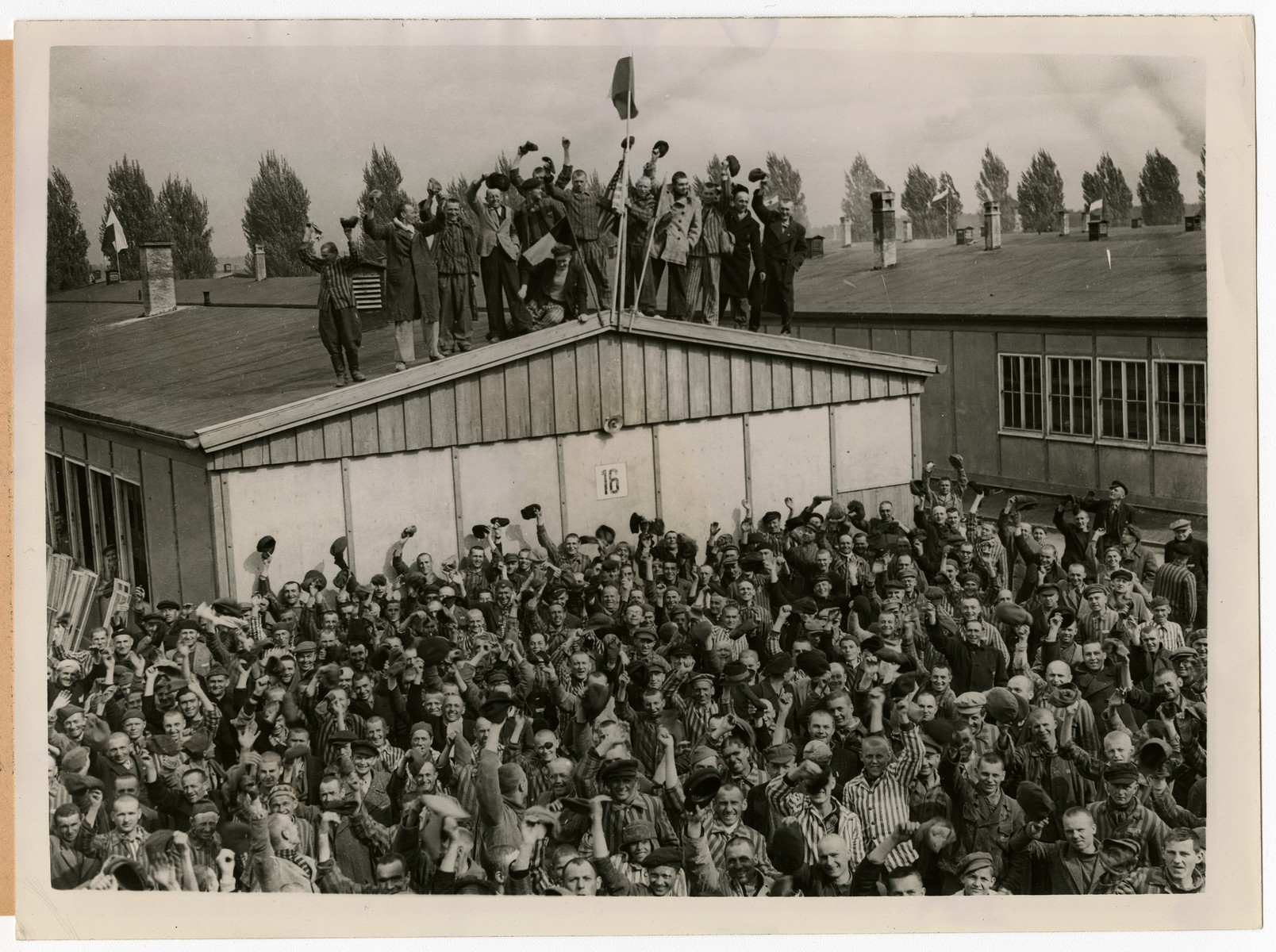 "View of Dachau concentration camp prisoners cheering on their liberators.   The original caption reads: Dachau Concentration Camp Horrors worse than those found in the German concentration camps of Buchenwald and Belsen were discovered in the stinking hell-hole of Dachau, captured by troops of the 42nd and 45th Infantry Division of the Seventh U. S. Army April 30,1945. More than 32,000 prisoners were liberated, among them some Englishmen, Canadians, and Americans. The camp was formally surrendered by an SS lieutenant carrying a white flag, accompanied by a Swiss Red Cross official, but SS troops opened fire as American troops approached the main entrance. The Germans were shot down. Three prisoners were electrocuted when they tried to burst through the electrified wire barrier to welcome the Americans. SS guards opened fire on other prisoners who went wild with joy and rushed to meet the liberating troops.   Prisoners with access to records said 9,000 people died of hunger, disease or shooting within the past three months at Dachau. Four thousand more perished during cold winter months. When Americans entered the camp, they found 50 open railway cars standing on a siding, apparently full fo dirty clothing but actually found to contain hundreds of corpses piled on top of each other. They also found a row of kennels where fierce dogs were kept to set after escaping men. They discovered gas extermination chambers, incinerators full of naked bodies, bodies marked for dissection and the bodies of several small children.   This photo shows: These political prisoners of the Germans were scheduled to be murdered by their Nazi guards but were saved by troops of the 42nd ""Rainbow"" Division. They secretly made flags of Allied nations as they heard the guns of the advancing liberators getting louder and louder. Keystone Photo"