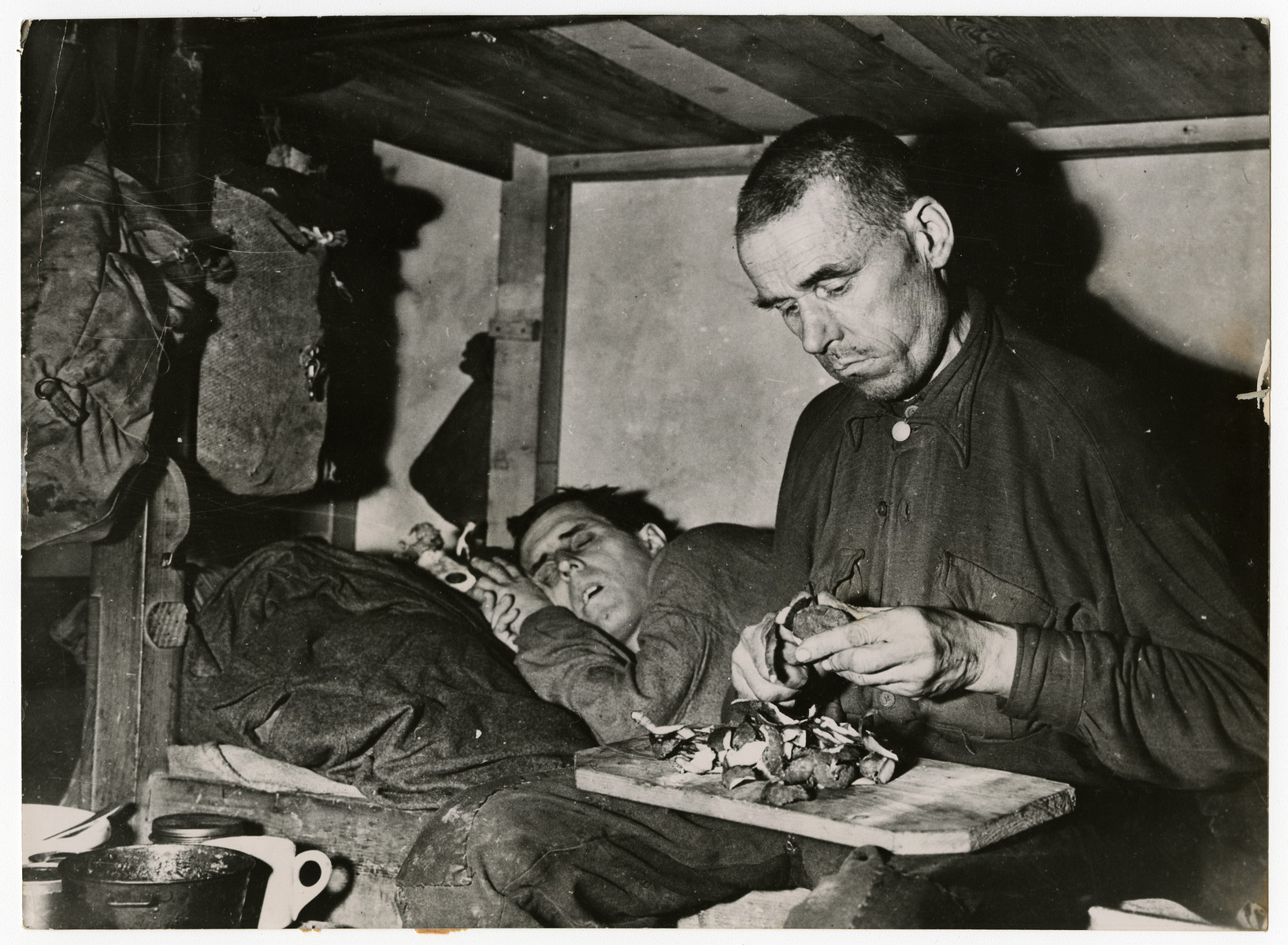 A liberated Russian prisoner peels potatoes in a former Nazi prisoner room.   Russians Liberated from Nazi Camp A liberated Russian prisoner of the Nazi peels potatoes in the filthy room where he spent almost a year until he was liberated by Allied troops who captured Munster April 3, 1945. His companion sleeps beside him in the unsanitary room of Stalag 6-F where approximately 10,000 German prisoners of various nationalities were kept by the Germans. U.S. Signal Corps Photo
