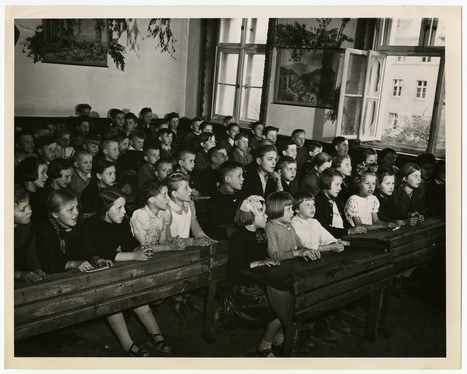 Polish children attend school in a displaced persons camp  Original caption reads:  Allies Speed Repatriation of Displaced Persons Inside Germany Liberated by the Allied armies in Germany, more than four million men, women and children, former slaves of the Nazi war machine, are free to return to their native lands as soon as repatriation machinery makes it possible. Meanwhile, these displaced persons are being gathered from the fields, factories and roadsides of Germany by Military Government authorities and placed in camps where they are registered, fed, clothed, sheltered and given medical attention.   Persons of almost a dozen nationalities, living in separate camps wherever possible, are guided along democratic lines in the operation of their communities. U.S. Army officials set up the displaced persons centers, guard the exterior of the camps and turn over the guidance problems to international teams representing the United Nations Relief and Rehabilitation Administrations. Once all the displaced persons are repatriated, UNRRA's job in Germany is finished, as it has nothing to do with Germans or military activities.   The Governments of Belgium, Holland, France and Luxembourg, have already brought thousands of their nationals home. By May 17, 1945, nearly 500,000 liberated prisoners-of-war and poltiical deportees were evacuated from German camps. The group included 604,950 Frnech, 120,140 British and 62,981 Americnas. All the Americans, 100,000 Frenchmen and 119,000 Britons were evacuated by air.   THIS PICTURE SHOWS: This is a Polish classroom established at the captured Wehrmacht post of Gniesnau Kasserno, near the east shore of the Rhine River across from Coblonz. The school was established by Lieutenent Colenol E.T. Hayes of Paducah, Kentucky, in an effort to get the childredn started towards an education. Many had spent their time playing war games, their favorite pastime being hand- grenade hunting. After finding the explosive they would toss them to eac