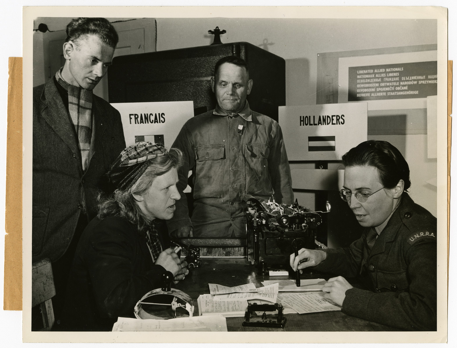 A Swiss woman speaks with a United Nations Relief and Rehabilitation Administration member about her capture and servitude during the Nazi Regime.   The official caption reads: Allies Speed Repatriation of Displaced Persons Inside Germany Liberated by the Allied armies in Germany, more than four million men, women and children, former slaves of the Nazi war machine, are free to return to their native lands as soon as repatriation machinery makes it possible. Meanwhile, these displaced persons are being gathered from the fields, factories and roadsides of Germany by Military Government authorities and placed in amps where they are registered, fed, clothed, sheltered and given medical attention.   Persons of almost a dozen nationalities, living in separate camps wherever possible, are guided along democratic lines in the operation of their communities. U.S. Army oficcials set up the displaced persons centers, guard the exterior of the camps and turn over the guidance problems to international teams representing the United Nations Relief and Rehabilitation Administrations. Once all the displaced persons are repatriated, UNRRA's job in Germany is finished, as it has nothing to do with Germans or military activities.   The Governments of Belgium, Holland, France and Luxembourg, have already brought thousands of their nationals home. By May 17, 1945, nearly 500,000 liberated prisoners-of-war and political deportees were evacuated from German camps. The group included 604,950 Frnech, 120,140 British and 62,981 Americans. All the Americans, 100,000 Frenchmen and 119,000 Britons were evacuated by air.   THIS PHOTO SHOWS: A Swiss woman who said she wandered across the German frontier near her home in 1941 and was immediately picked up by SS men to be placed into servitude tells her story to an UNRRA representative as two other displaced persons look on at Fort Ehrebritstein.