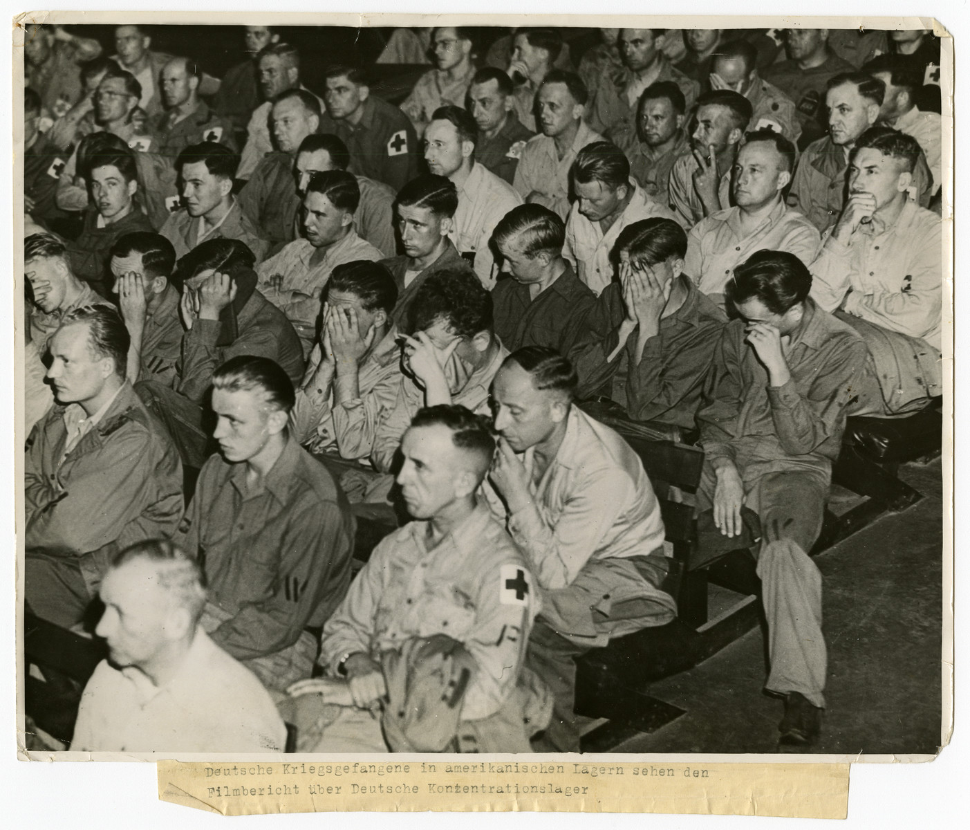 German prisoners of war are forced to watch an atrocity  film on German concentration camps.  Original caption reads:  Deutsche Kriegsgefangene in amerikanischen Lagern sehen den Filmbericht über Deutsche Konzentrationslager   [German prisoners of war held in an American camp watch a film about German concentration camps.]