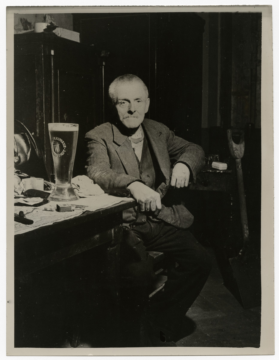 "Wilhelm Guillion, a janitor of a beer hall, poses at the table where Hitler first laid plans for the formation of the Nazi Party.   Original caption on the back of the photo reads: Nazi Meeting Place Wilhelm Guillion, 76-year-old civilian of Munich, sits at a table where Hitler first laid plans for the formation of the Nazi Party. Guillion is a janitor of a building containing one of the beer houses where the original Nazi Party meetings were held. In the cabinet behind him, many original Hitler documents regarding the party's formation were found. Munich, which was the scene of Hitler's abortive beer cellar ""putsch"" in 1923, was captured April 29, 1945, by troops of the Seventh U.S. Army. Associated Press Photo."