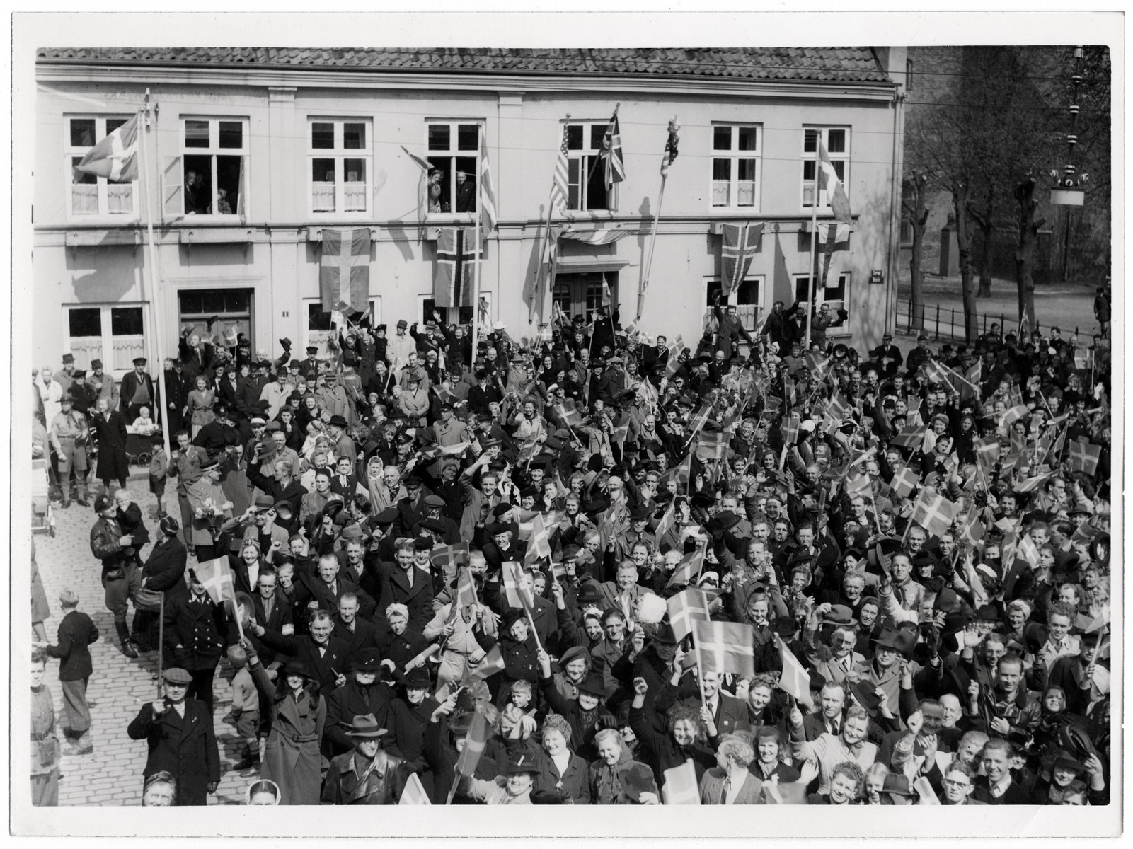 "Danish civilians celebrate their liberation.  Original Caption: ""Liberation of Denmark. Scenes of the greatest enthusiasm greeted an R.A.F. official photographer and the pilot of an Auster aircraft when they flew into liberated Denmark and landed beside the little town of Tonder. 6.5.45""  This photo shows: ""A general view of the crowds celebrating their liberation in the town square of Tonder. The Allied flags can be seen in the background."""