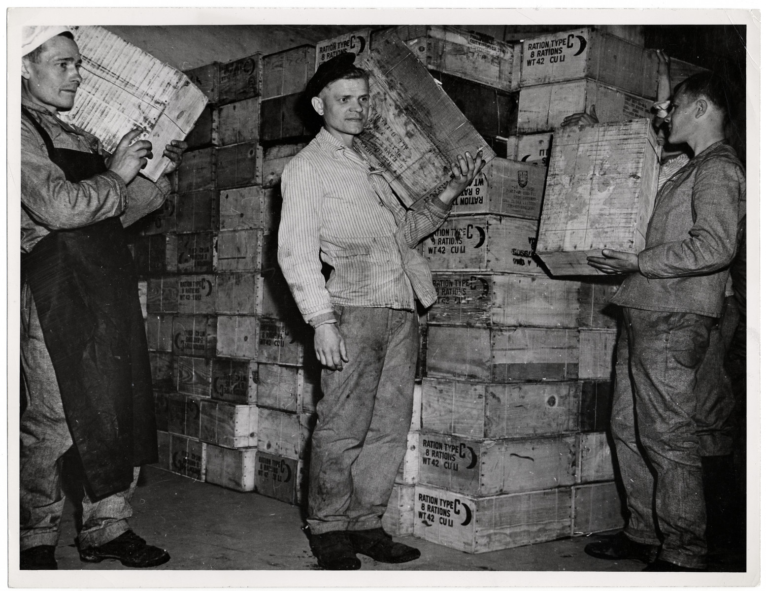 "Recently liberated Soviet POWs enjoy American food rations.  Original Caption: ""Russian prisoners of war liberated in Hemer, Germany, by the Ninth US Army celebrated May Day, 1945 by holding a banquet of 'C' rations. Infantrymen of the 75th Infantry Division are shown handing out boxes of the rations for the banquet. There were 22,000 Russians in the Hemer camp, 9,000 of them hosptial cases suffering from tuberculosis, dysentery, typhus and malnutrition."""