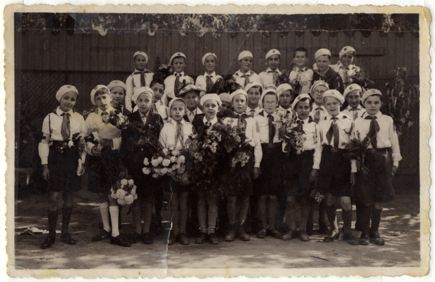 Group portrait of children from the public school in Brasov Romania holding bouquets of flowers.    They are probably dressed up in honor of the birthday of King Carol II, wearing the school uniform dictated by the Fascist regime.  Among those pictured are the donor, Gheorghe Joszef (bottom row, sixth from the right) and Joan Janosi (top row, sixth from the right).