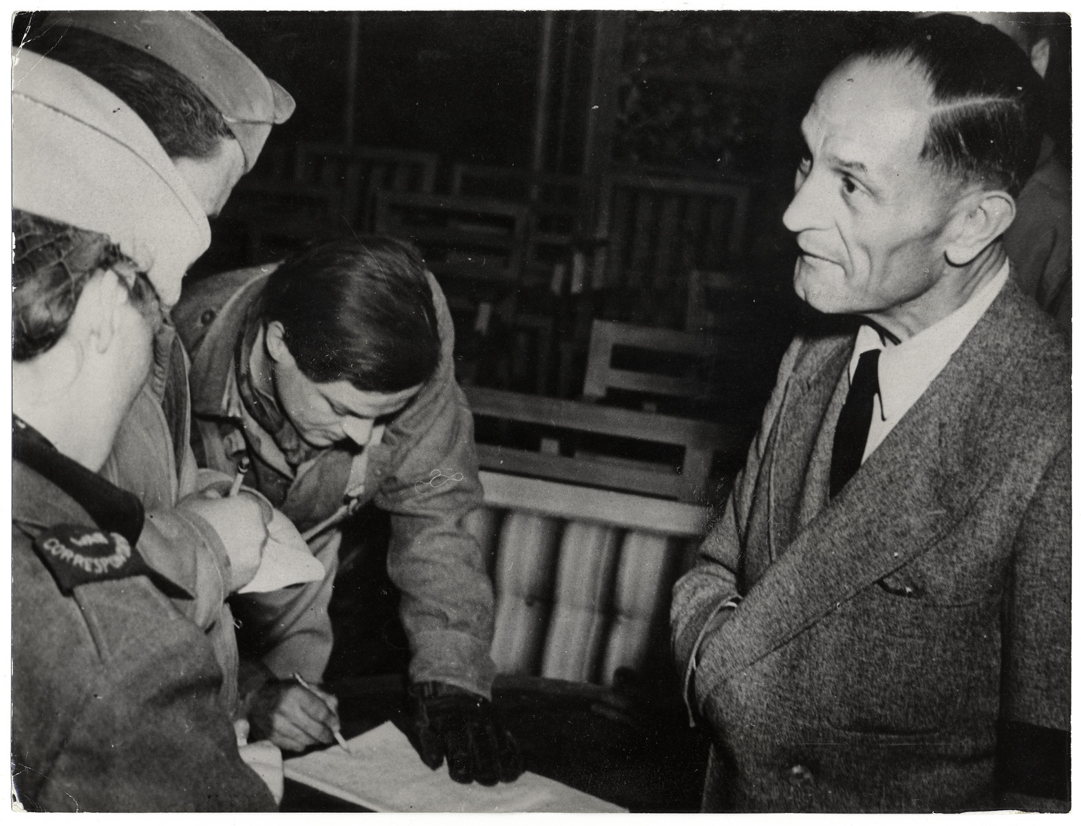 "Pastor Martin Niemoeller speaks to reporters after his release from concentration camp.  Original Caption: ""This and wan after long months of solitary confinement, Lutheran Pastor Niemoller, who defied Hitler at his parish in Dahlem, Berlin, tells his story to allied war correspondents after Allied troops had released him from the prison camp at Alb in the Alpine mountain Dolomite Valley. He was one of 133 bold men and women of Europe who were imprisoned at this camp for defying Hitler. Secret orders for the execution of the most famous personalitites among them had been issued days ago by the Gestapo. They were saved by the arrival of the Fifth Army troops."""