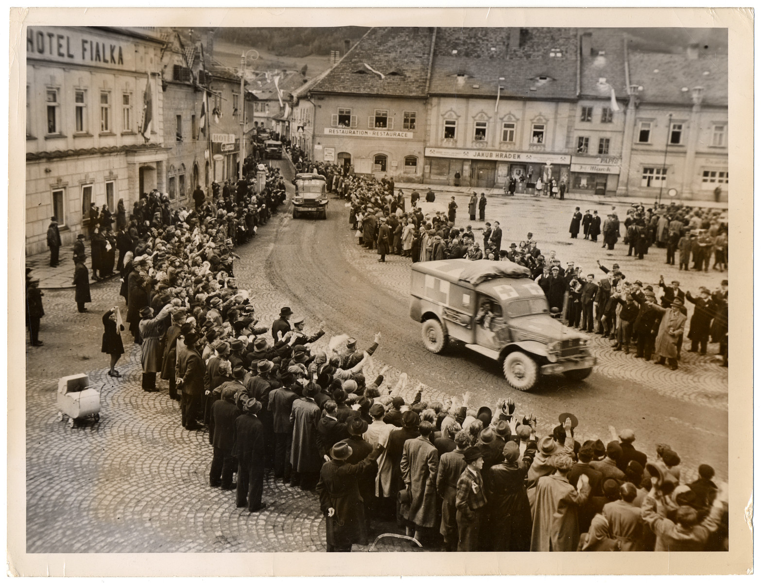 """Czech civilians cheer American soldiers.  Original Caption: """"Civilians of Schuttenhoffen, Czechoslovakia, line up to cheer the entrance of Fourth Armored Division forces of the Third US Army, who liberated their town from the Germans. This photograph was taken May 6, 1945, while fighting was still raging in the country. This continued even after the German high command signed unconditional surrender terms May 7, 1945, although the Germans in Czechoslovakia were ordered to cease firing and were threatened with heavy penalties. Czechoslovakia was invaded by the Germans in 1939 and was reentered by Allied forces May 1, 1945."""""""