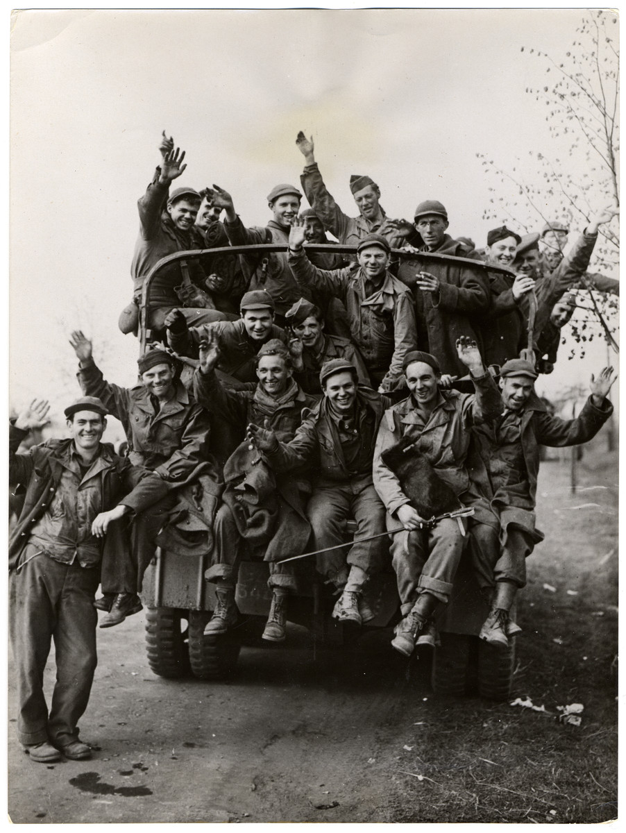 "Recently liberated American POWs wave as they leave their camp.  Original Caption: ""American prisoners of war, recently liberated by a combat command of the US Fifth Armored Division, wave as a truck takes them from Tangermunde, Germany, where they were held to the rear. The soldier, second from the right seated in the back end of the truck takes a captured German sword with him."""