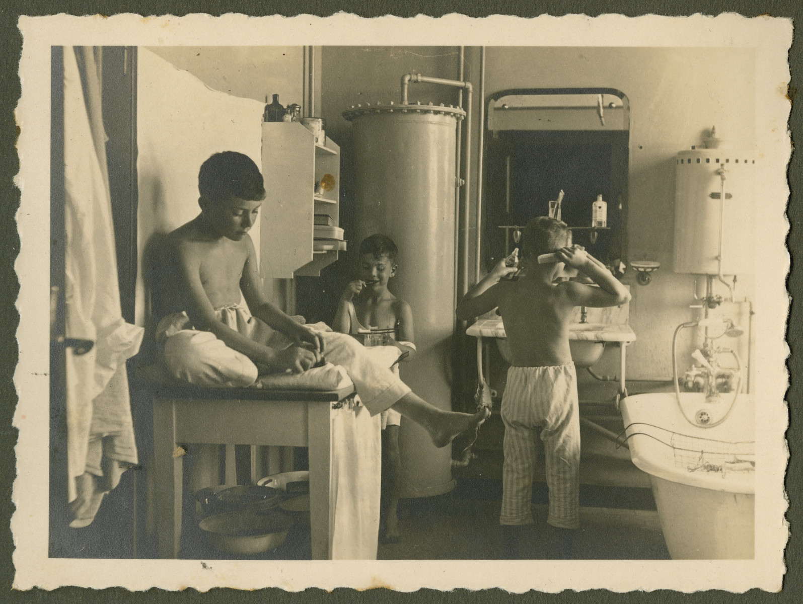 "Page from a photo album documenting one day in the life of the Gans brothers, Carl, Manfred and Theo.  This page is entitled ""Hair, teeth, feet -- why each morning""?"