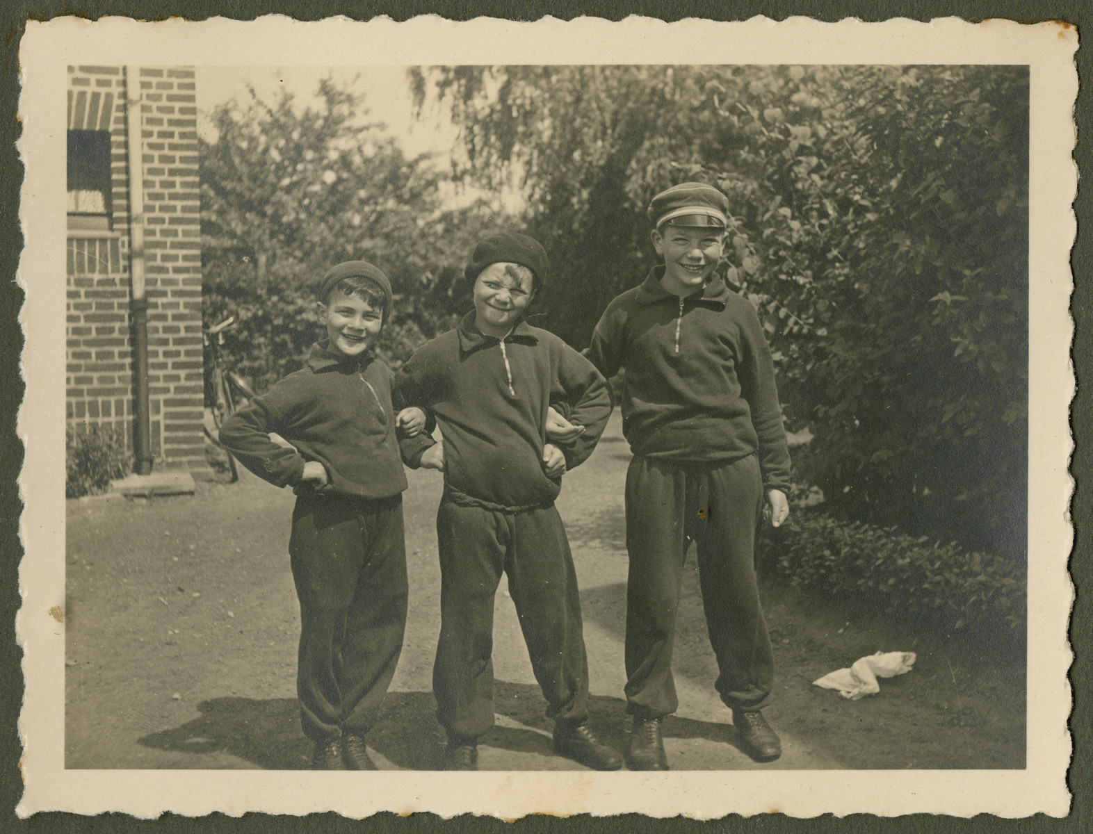 Page from a photo album documenting one day in the life of the Gans brothers, Carl, Manfred and Theo.  Ready for sports.  The boys belonged to a Catholic Sports Club.