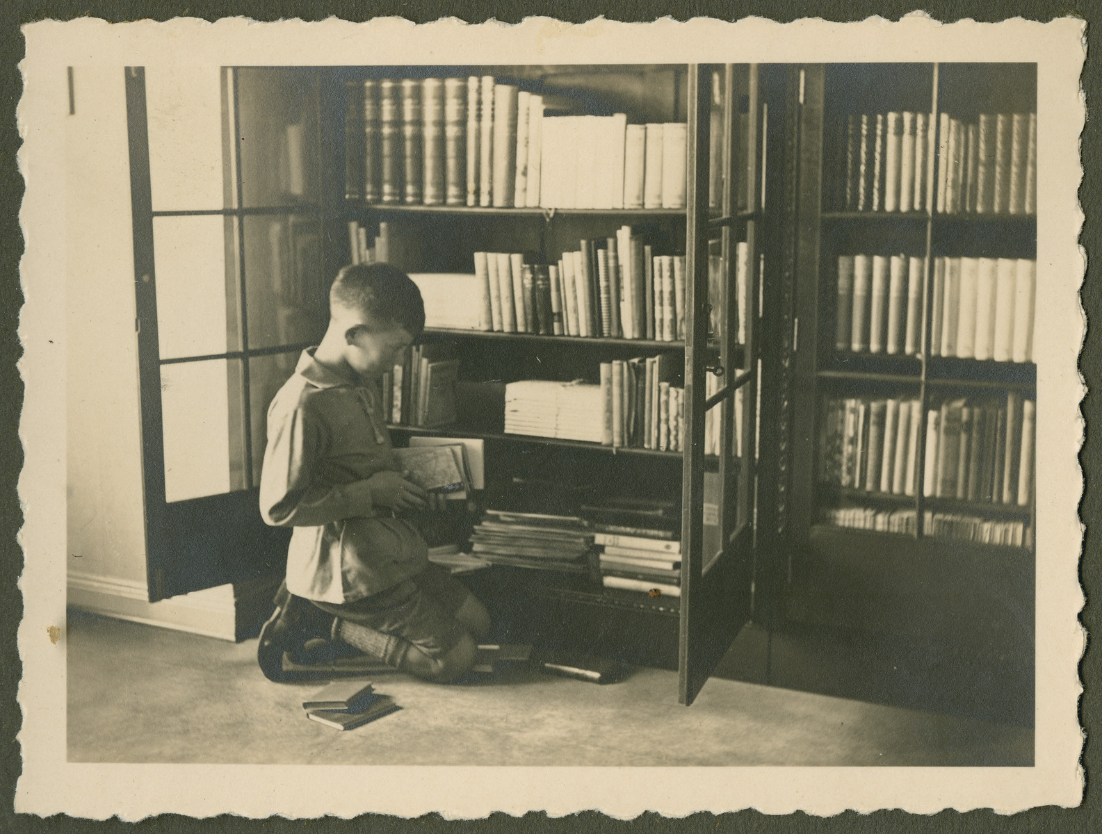 """Page from a photo album documenting one day in the life of the Gans brothers, Carl, Manfred and Theo.  This page is entitled """"The bookworm."""""""