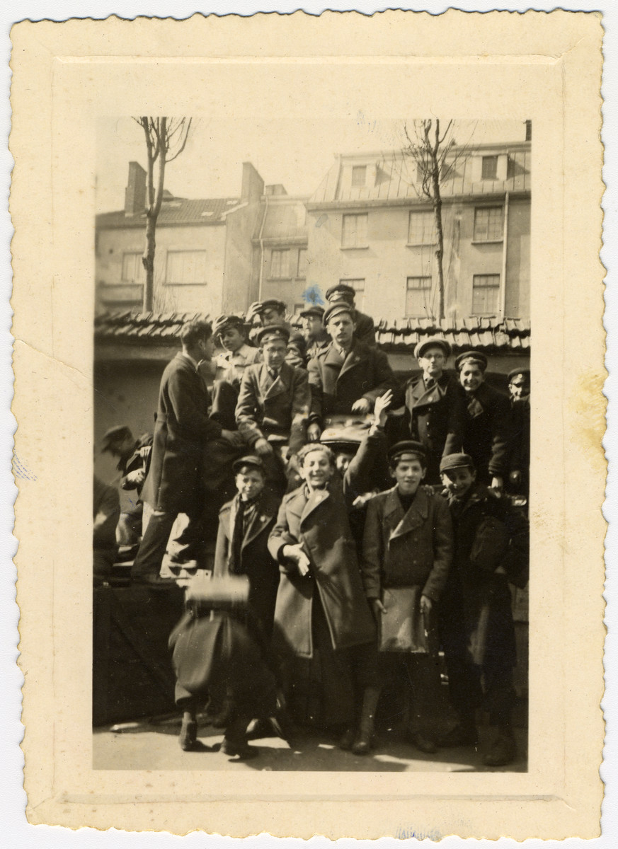 Group portrait of Bulgarian Jewish boys in the courtyard of a synagogue in Sofia.  They have climbed on top of crates that hold supplies that were gathered for Greek Jews who were passing through Sofia during their deportation.  Among those pictured are Albert Farhi.