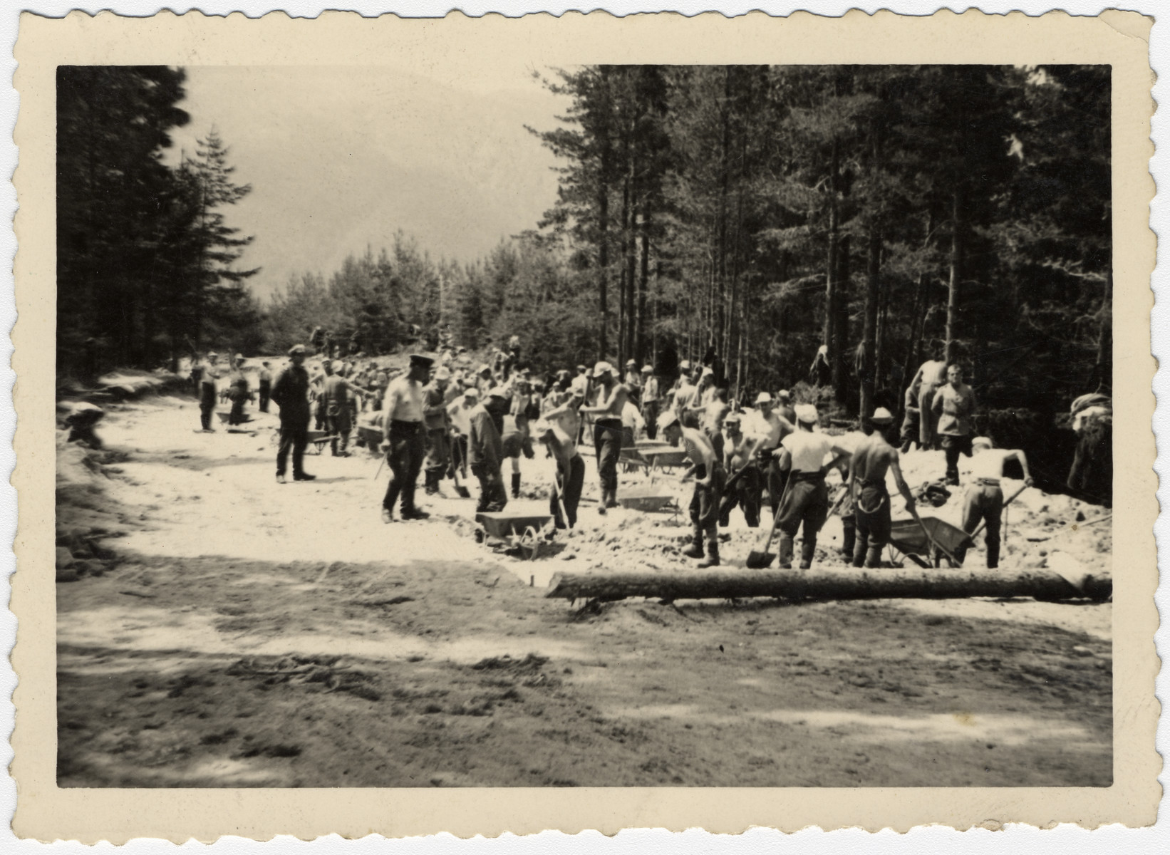 Bulgarian Jews dig a road in a forced labor brigade.  Standing on the right in his army uniform is Nissim Farhi.  In Bulgaria, Jewish officers were allowed to serve as officers in labor brigades and wear their uniforms.