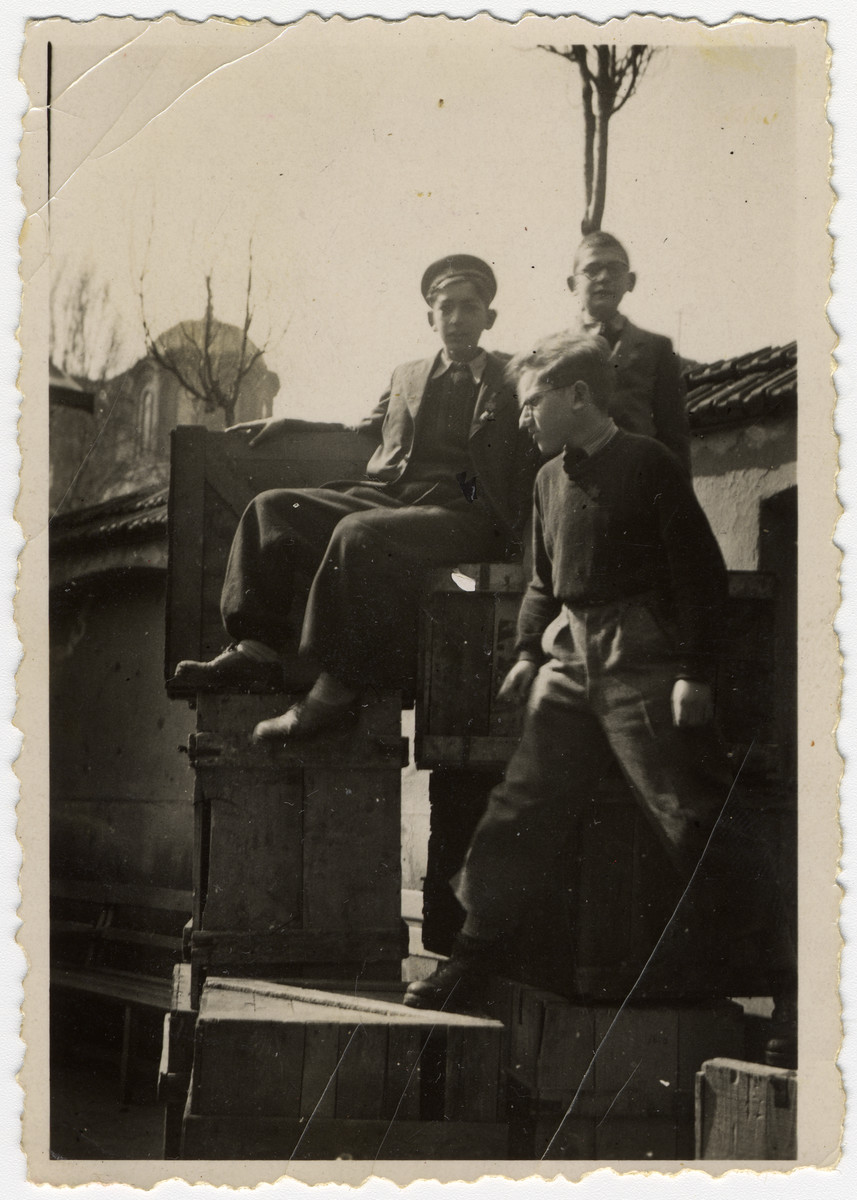 Group portrait of Bulgarian Jewish boys in the courtyard of the synagogue.climbing on top of crates holding supplies that were gathered for Greek Jews who were passing through Sofia during their deportation.  Among those pictured is Albert Farhi.