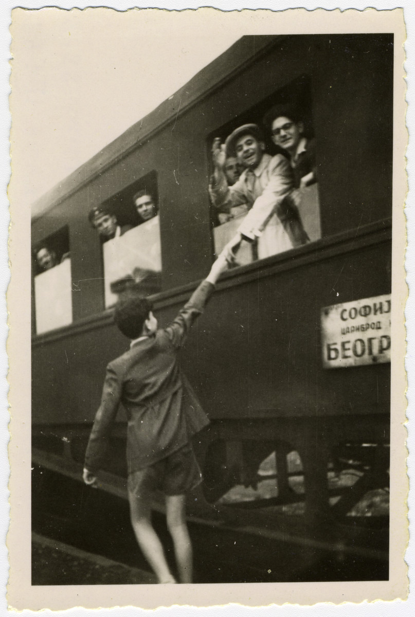 "David Farhi leaves for Paris by train accompanied one stop by his younger brother Albert.  A third brother Moise runs along-side the train.  The sign on the train reads ""Train to Belgrad""."