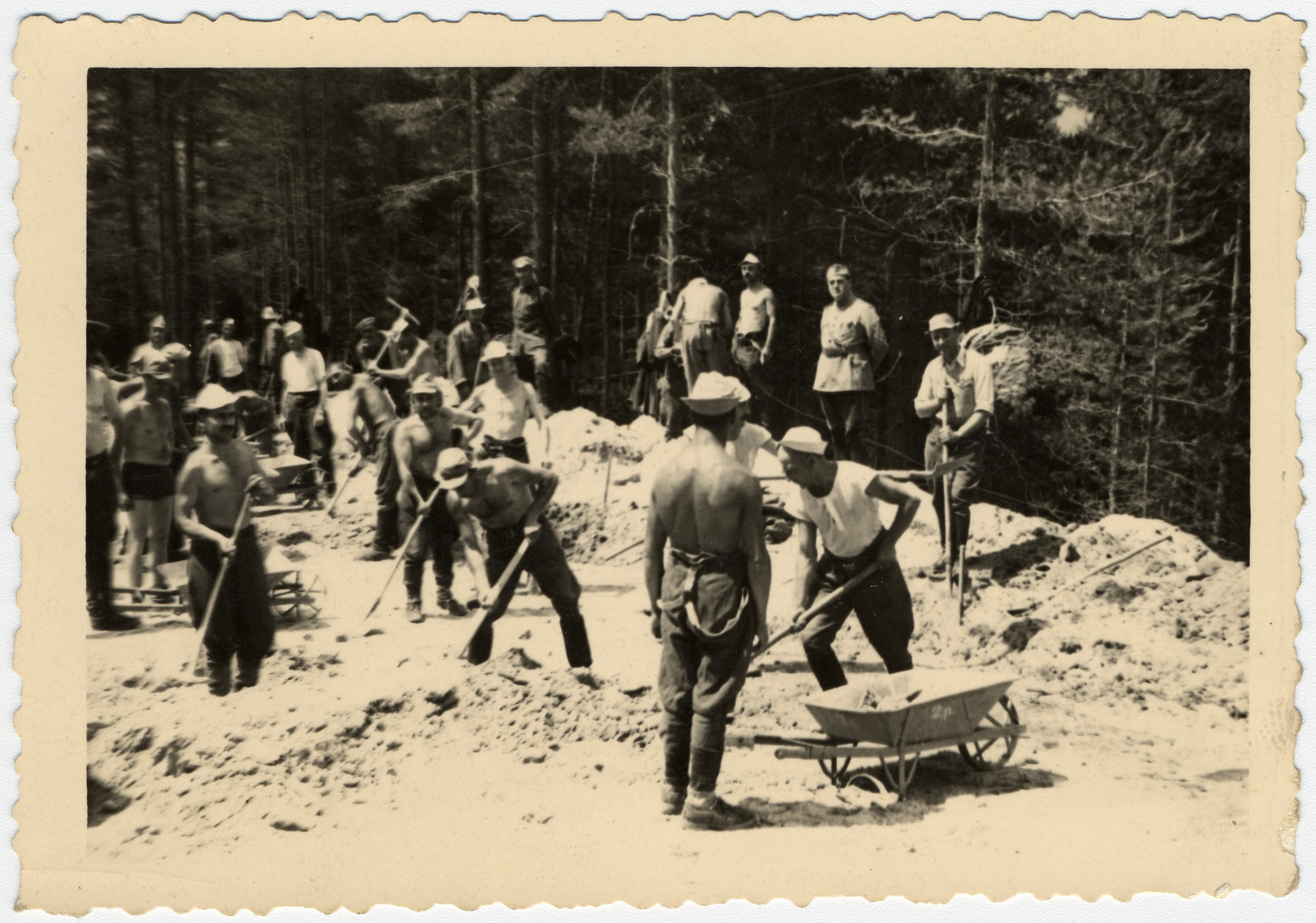 Bulgarian Jews dig a road in a forced labor brigade.  Standing in the back in his army uniform is Nissim Farhi.  In Bulgaria, Jewish officers were allowed to serve as officers in labor brigades and wear their uniforms.