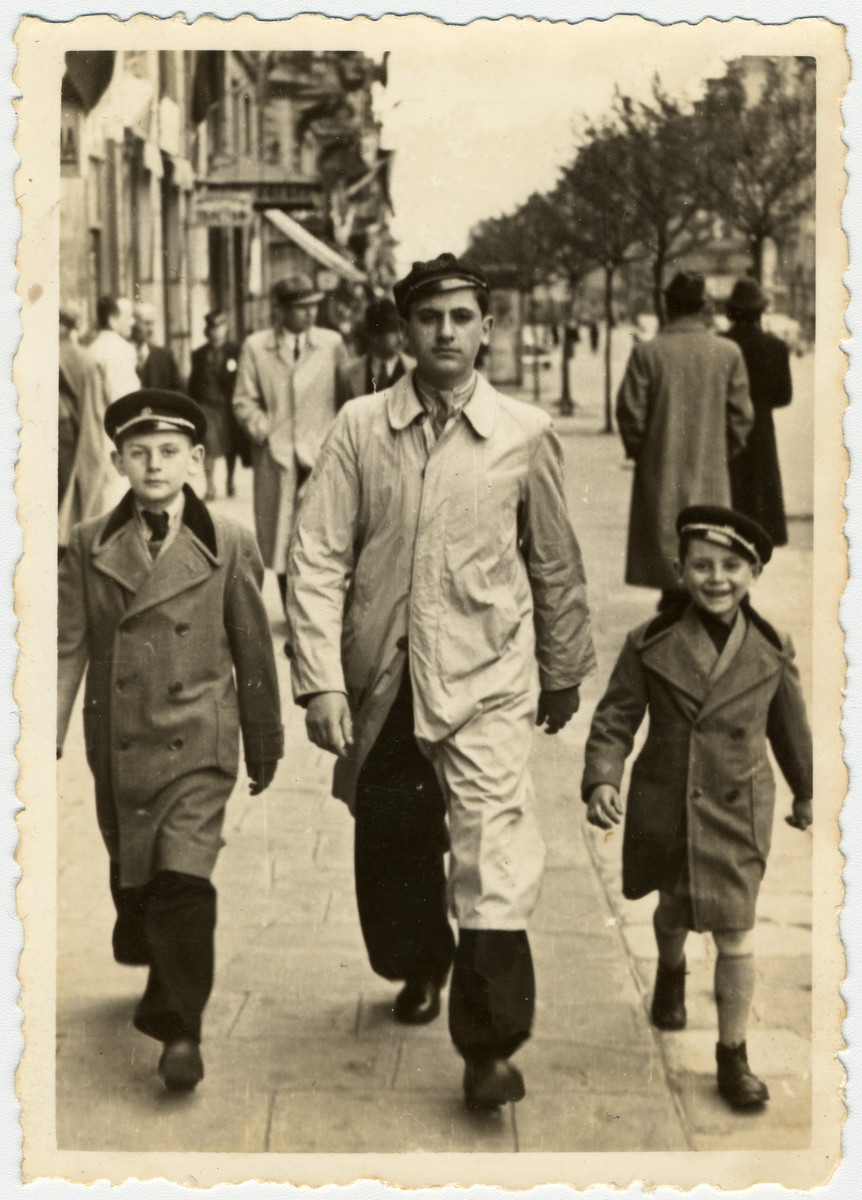 Three Jewish brothers walk down a street in Sofia en route to a concert.  From left to right are Albert, David and Moise Farhi.