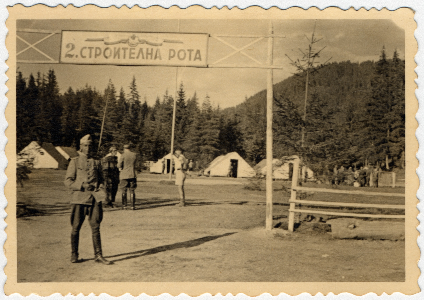 View of the entrance to the 2nd Constuction Company labor battalion in Bulgaria.  Standing in front is Avramoff