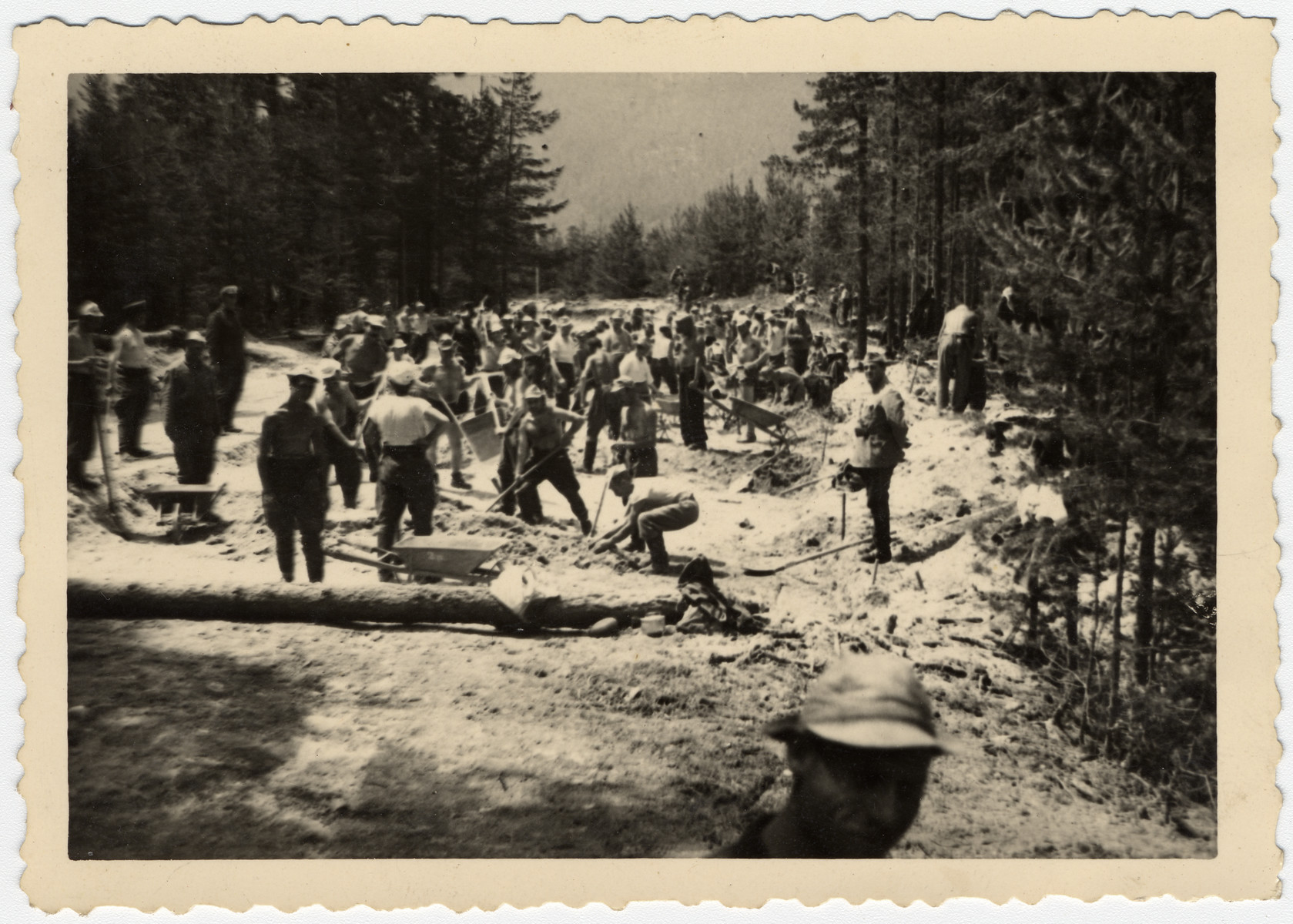 Bulgarian Jews dig a road in a forced labor brigade.  Standing at the right in his army uniform is Nissim Farhi.  In Bulgaria, Jewish officers were allowed to serve as officers in labor brigades and wear their uniforms.