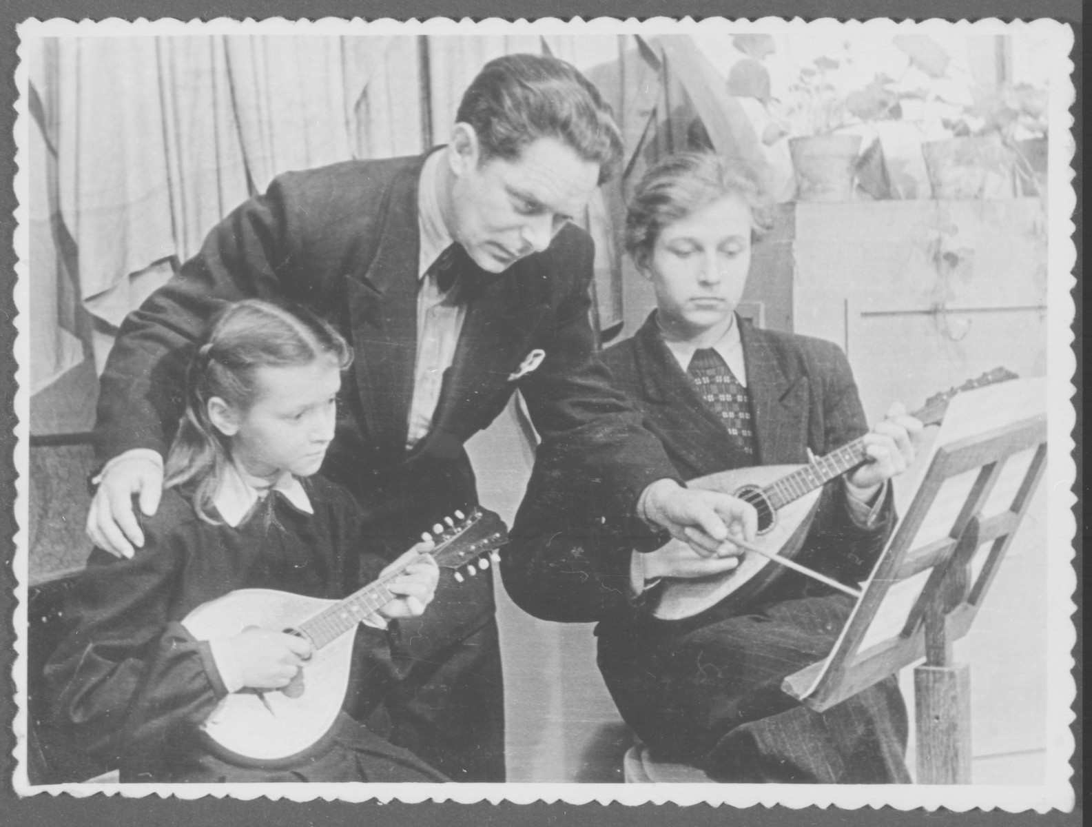 Elja Heifecs gives mandolin lessons to two students.