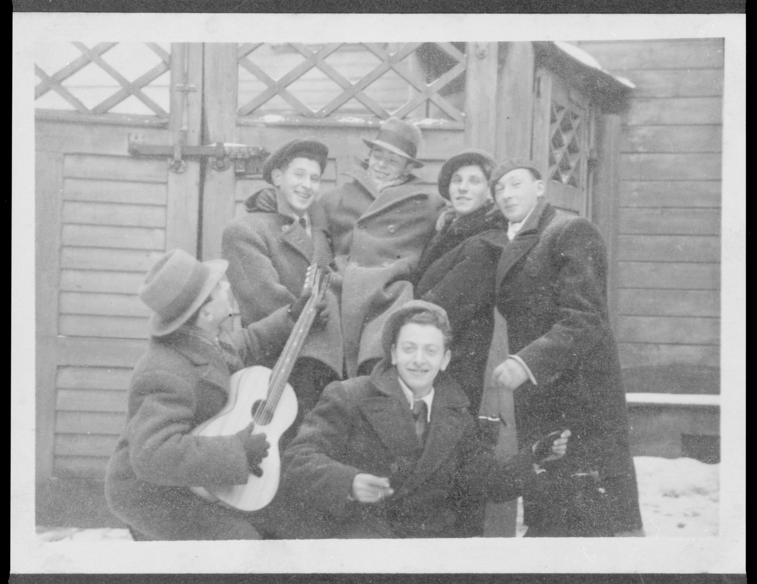 A group of Latvian Jewish friends, one playing the guitar, poses outside a building in the snow.  Pictured in the back center is Elja Heifecs.