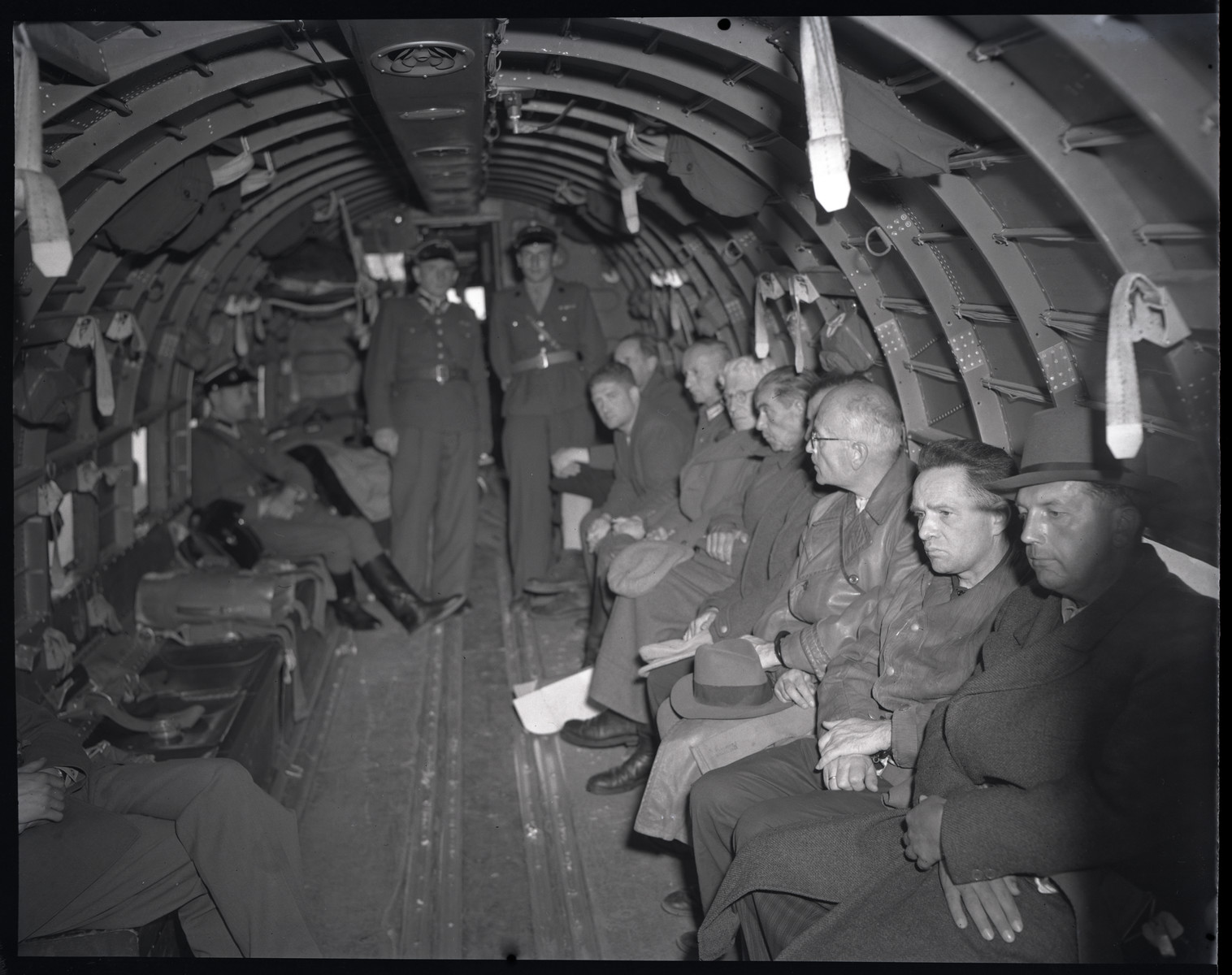 Rudolf Hoess, among other war criminals, is being transported to Poland for trial.  Also picutred in the right rear is Josef Buehler, deputy governor of the General Government.