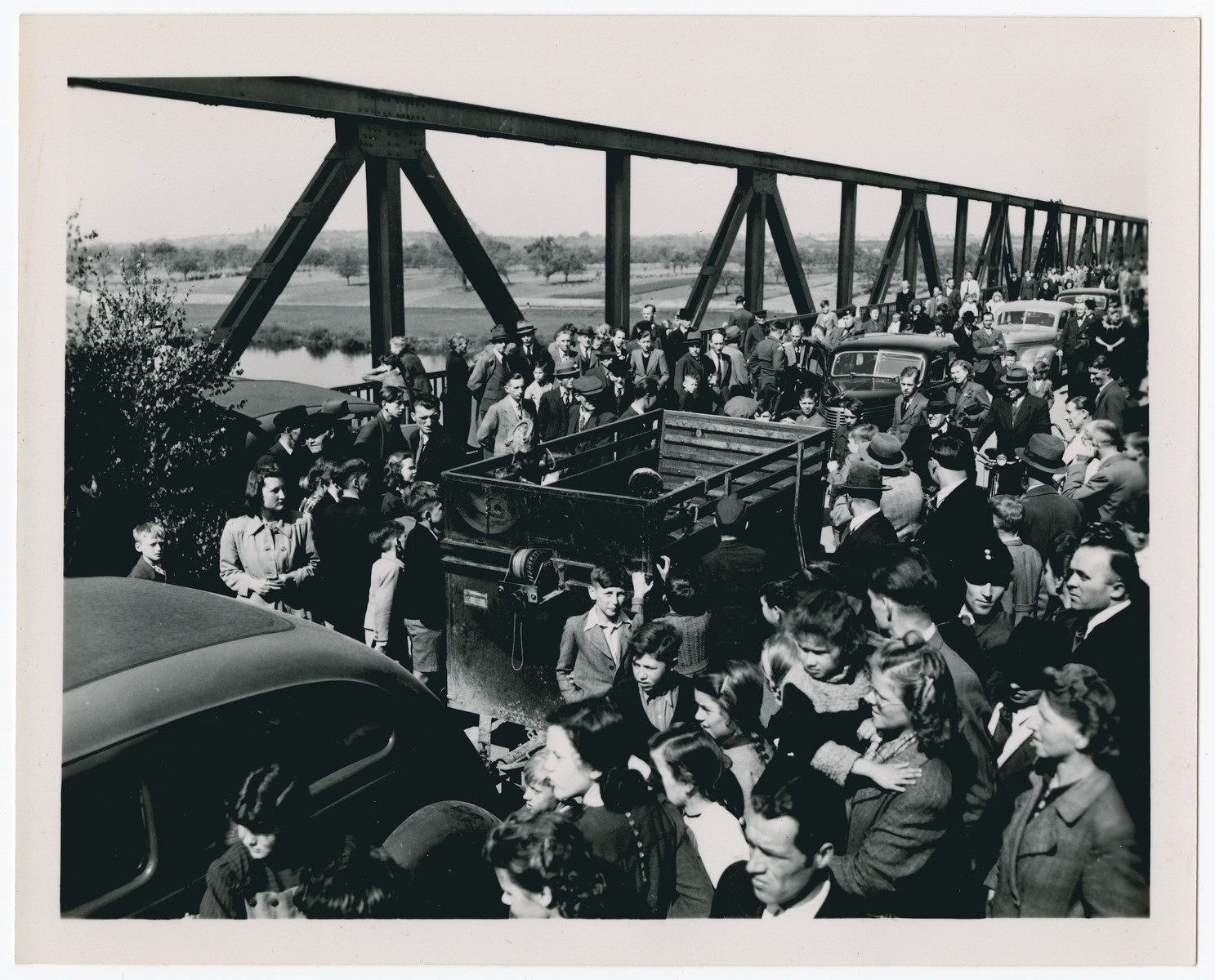 [Refugees stream across a bridge in postwar Germany.]  Caption not confirmed.