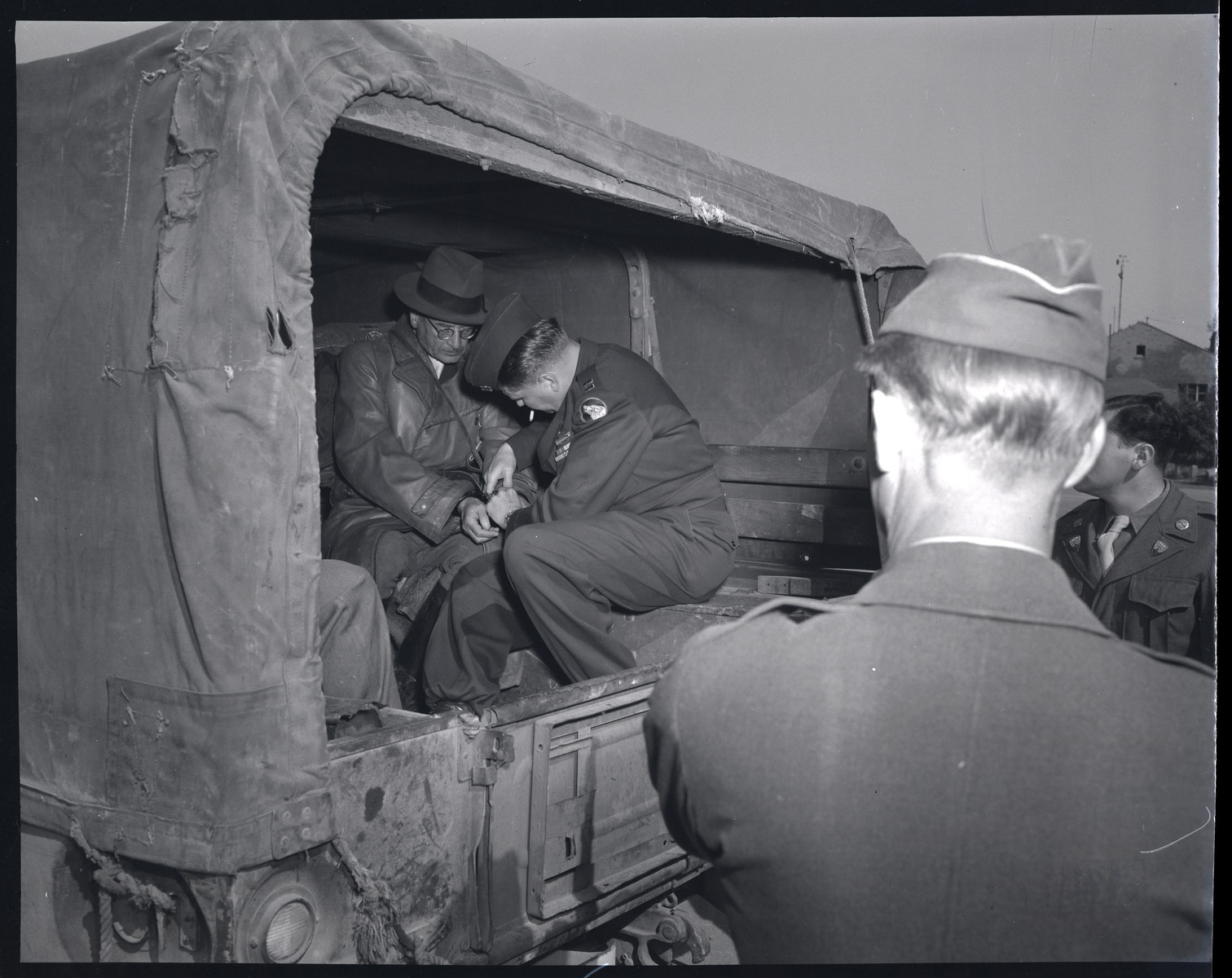 Kurt von Bursgsdorff, former governor of Krakow, is  transported by American soldiers in shackles.