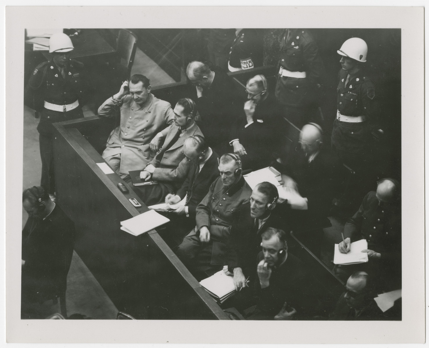 Photograph of the defendant's dock at the International Military Tribune in Nuremberg.   Seated in front row from left to right: Goering, Hess, von Ribbentrop, Keitel, Kaltenbrunner and Rosenberg.