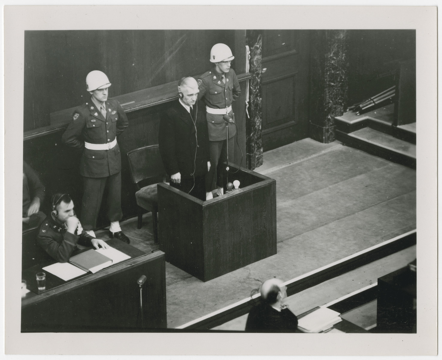 Photograph of defendant [probably Hjalmar Schacht] stands at the defendant's dock at the International Military Tribunal.  Schacht was later acquitted of charges.