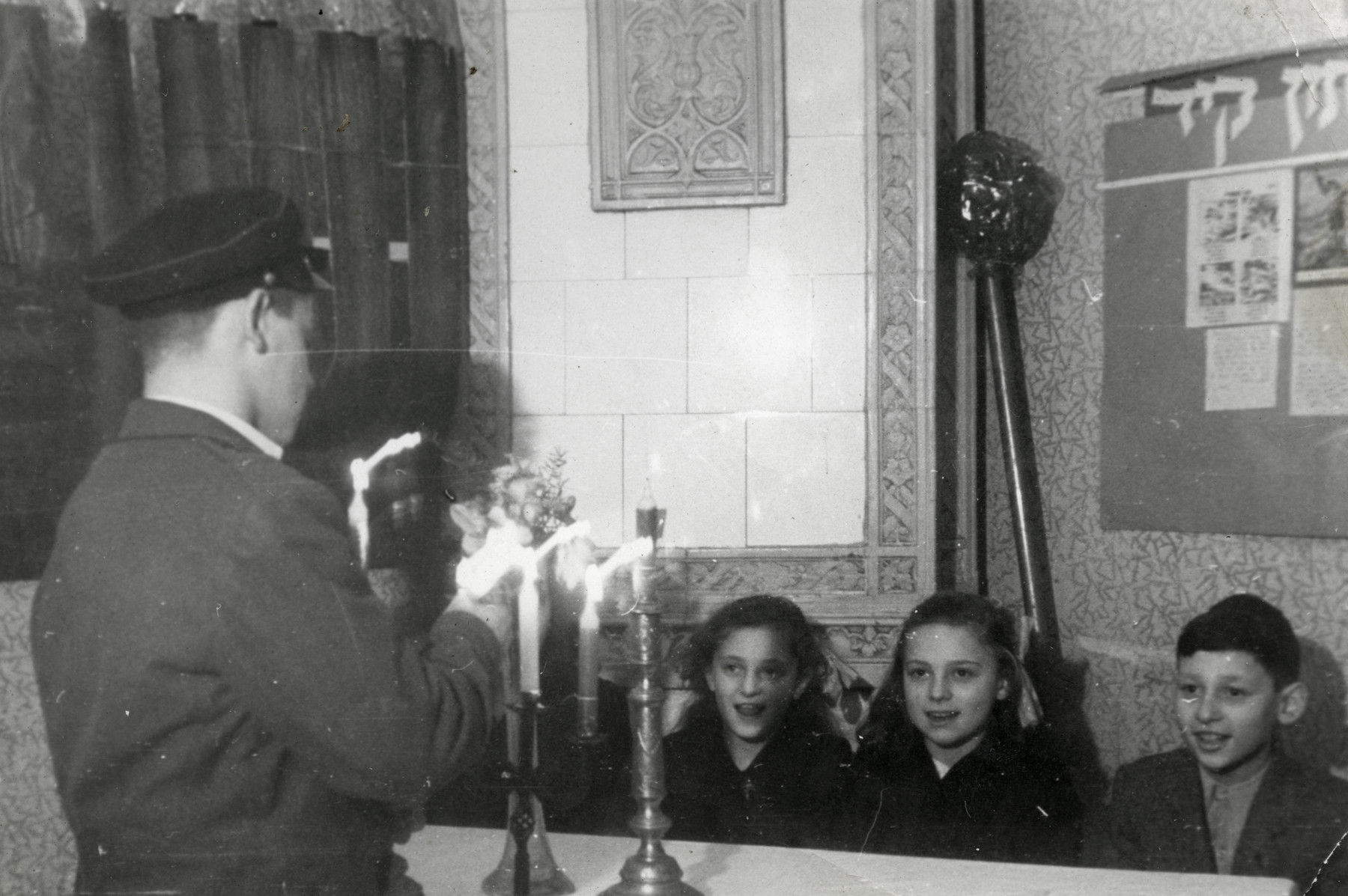 An older child lights candles at a celebration at the Lodz Coordinatsia orphanage.