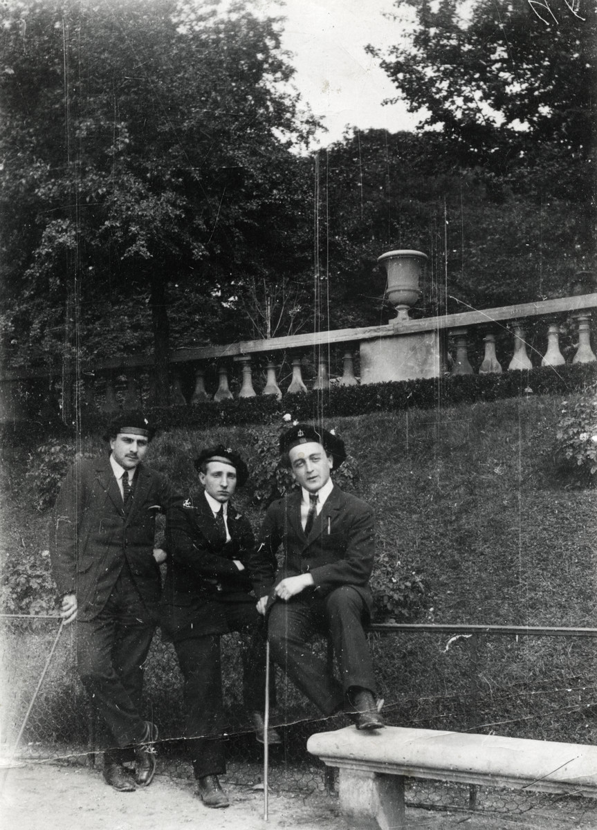 Portrait of three young men wearing school uniforms and hats, carrying canes.  Matthieu Mueller is on the far right.